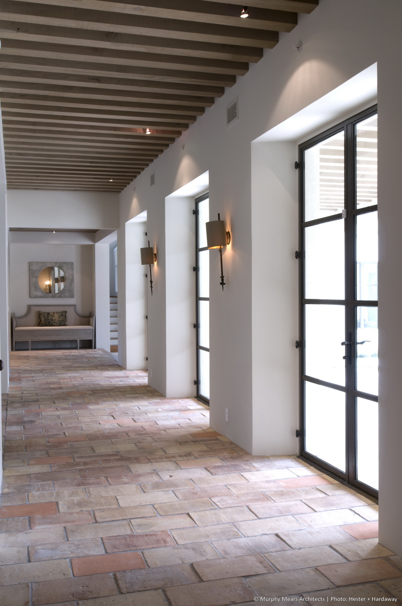 Lindenwood Residence - Main central corridor with imported terra cotta tile and a load-bearing wood beam ceiling structure milled from trees grown on site.