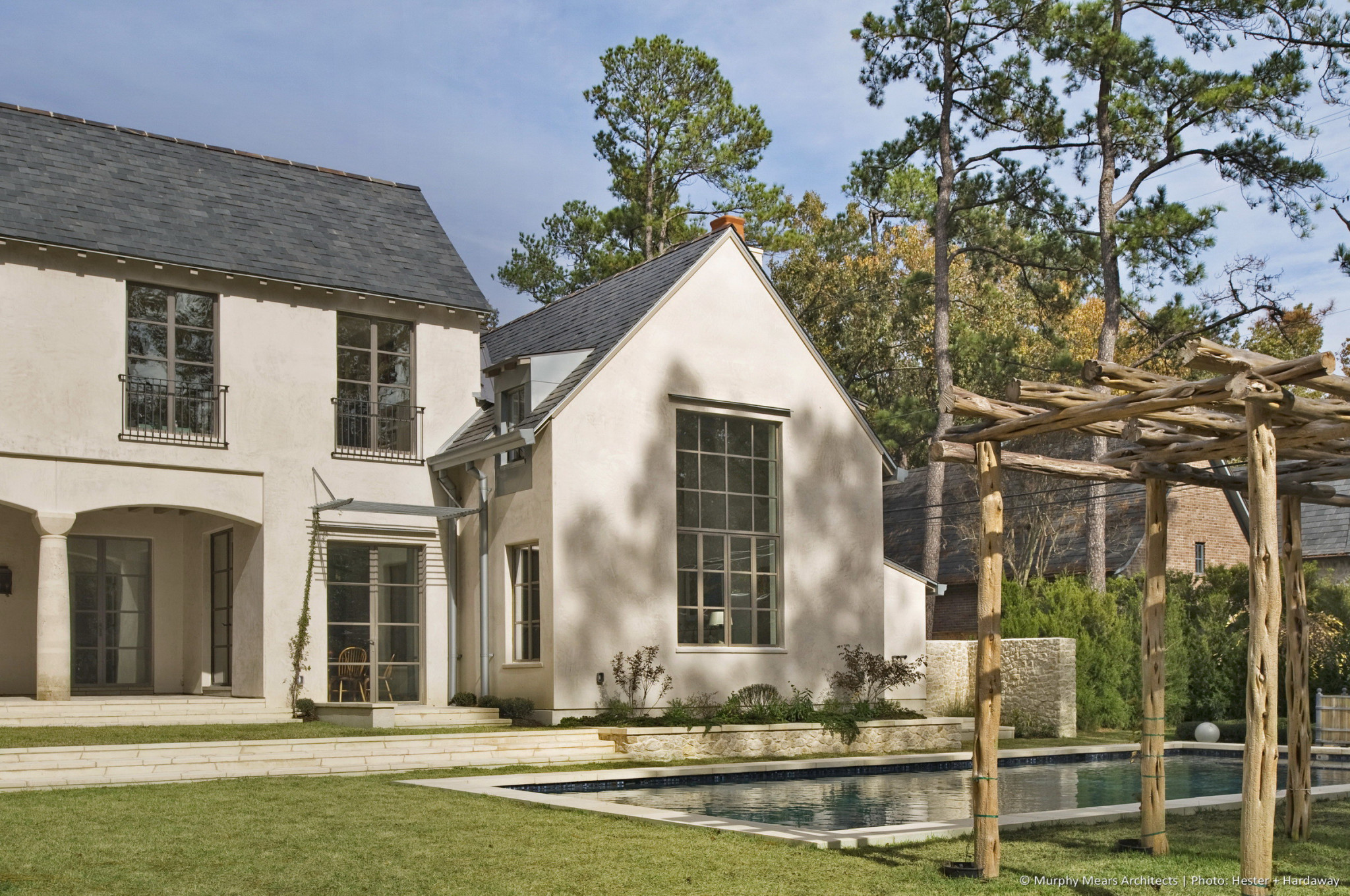 Lindenwood Residence - Modern take on an English arts and crafts style home, overlooking a backyard with the pool set within a green landscape.