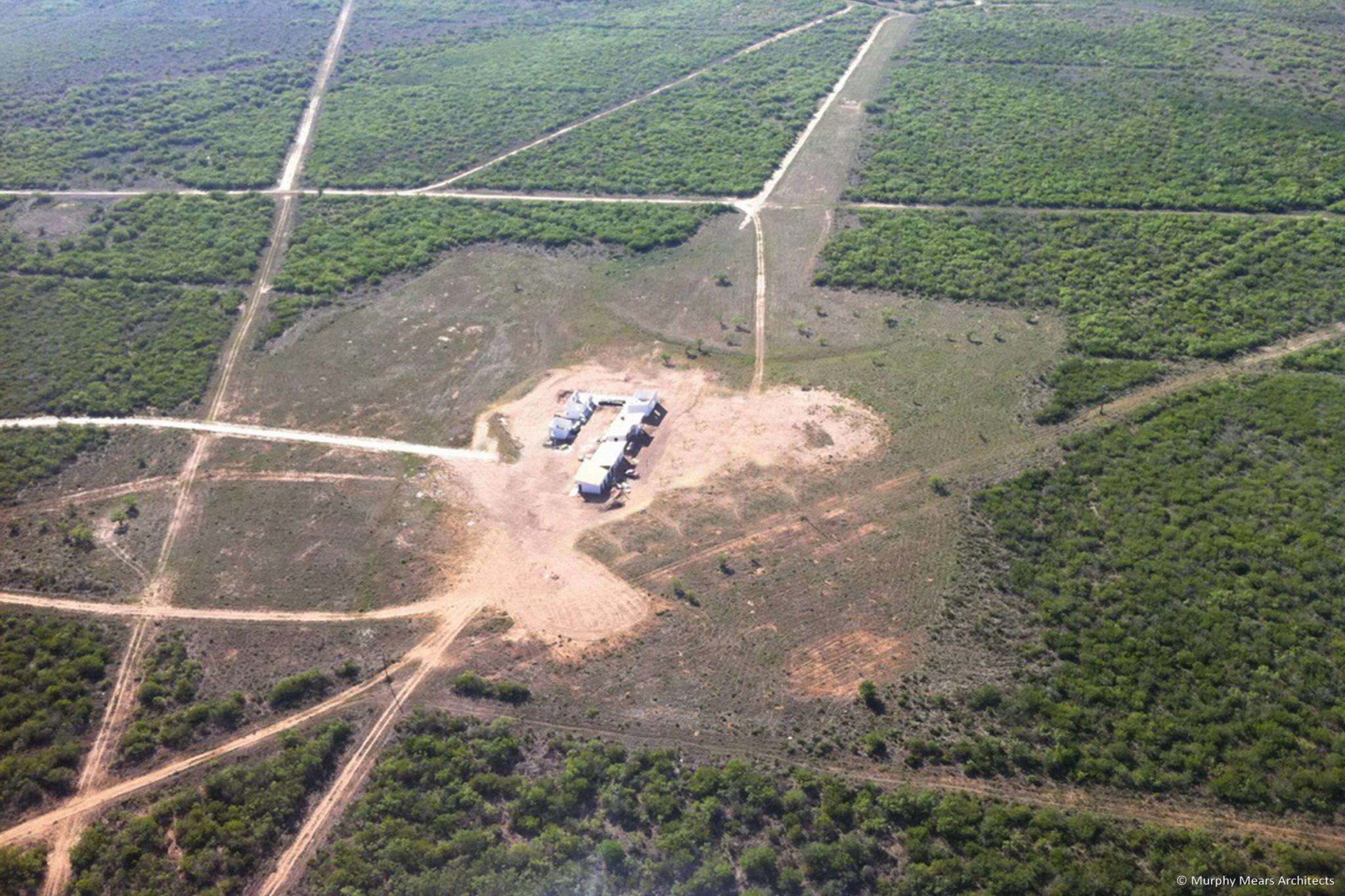 aerial view of ranch compound under construction with senderos extending into south texas landscape