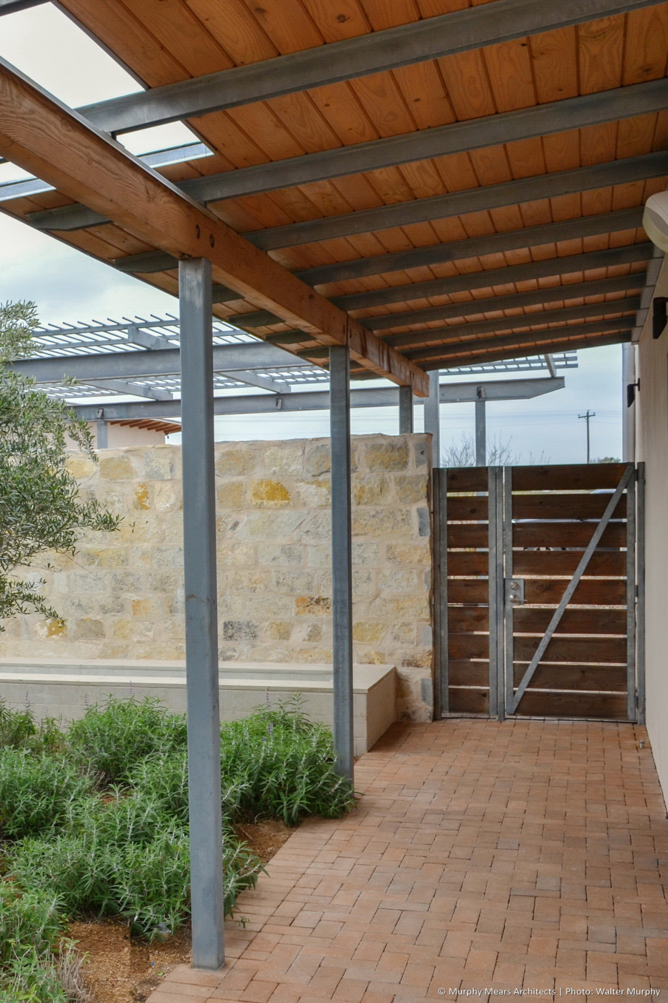 galvanized steel and wood entry gate beneath covered walkway with brick pavers adjacent to stone wall
