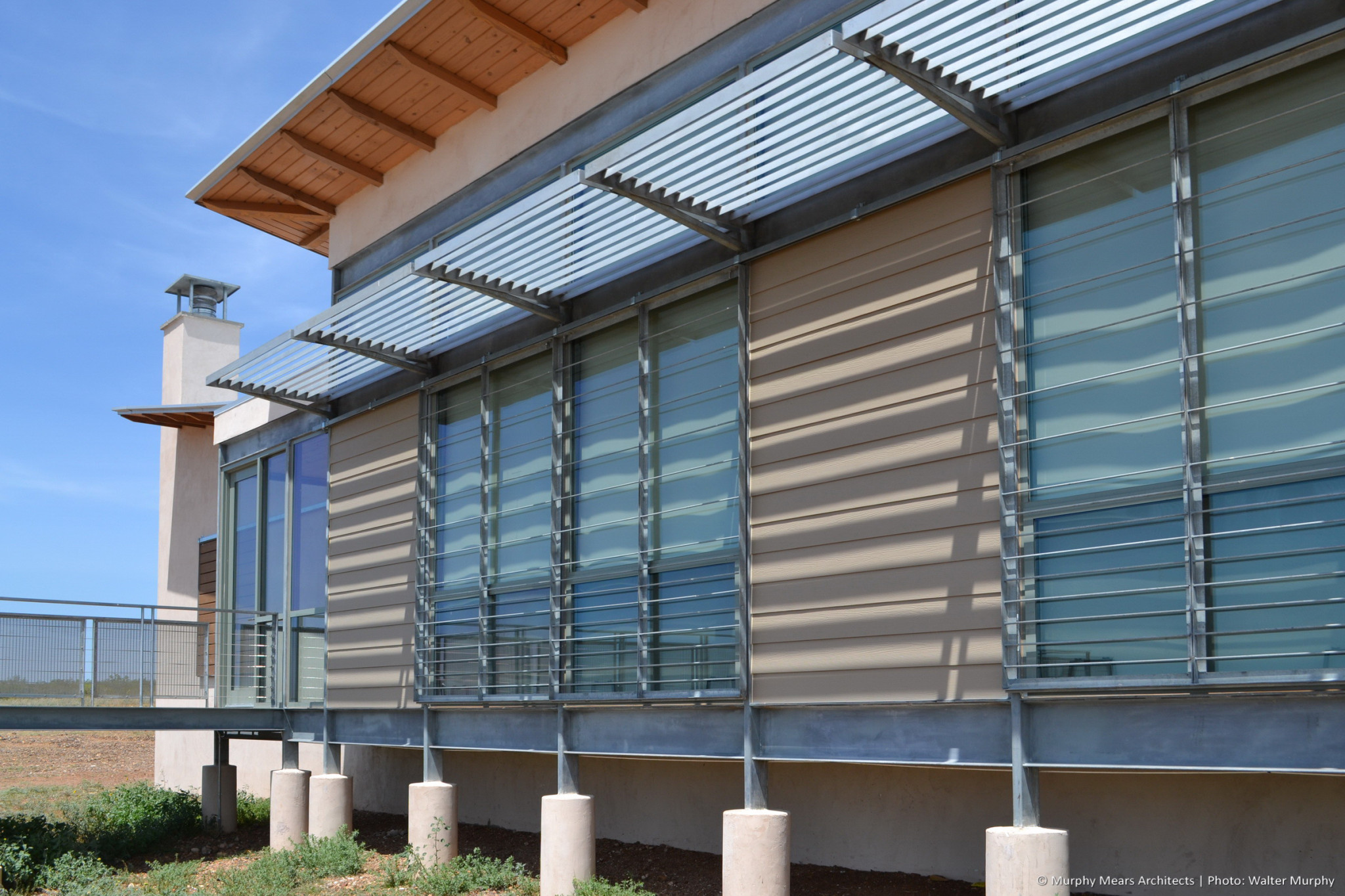 galvanized steel fin awning and wood roof casting shadows on window wall with lapped hardie siding accent panels
