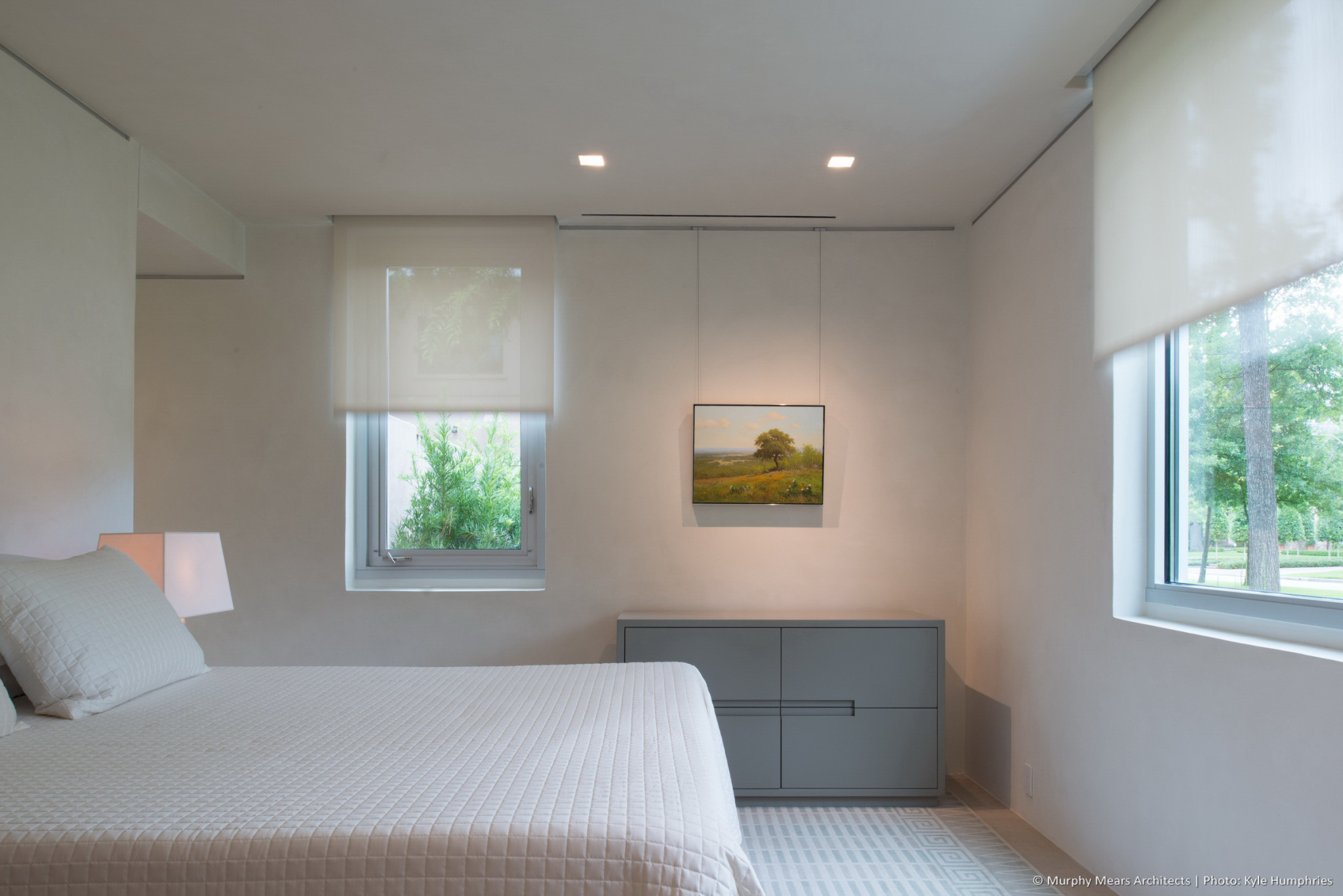 Guest bedroom with automated shades raising into hidden pockets above the West and South windows.