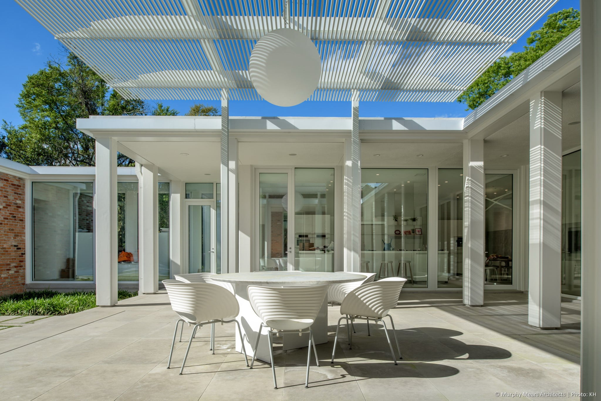 Outdoor dining beneath the aluminum and steel trellis on the upper terrace.