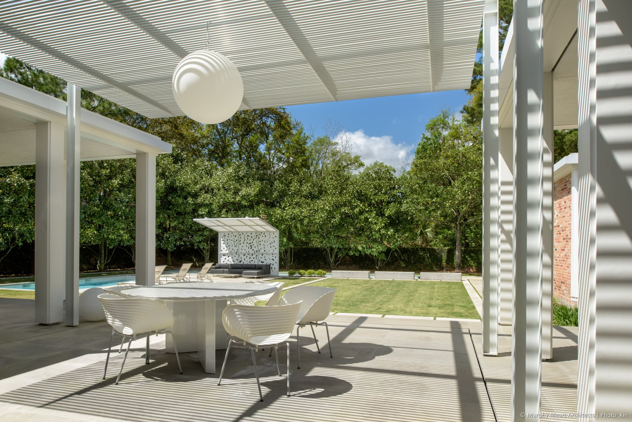 Outdoor dining area beneath the aluminum and steel trellis, overlooking the central lawn, with the pool terrace shade canopy beyond.