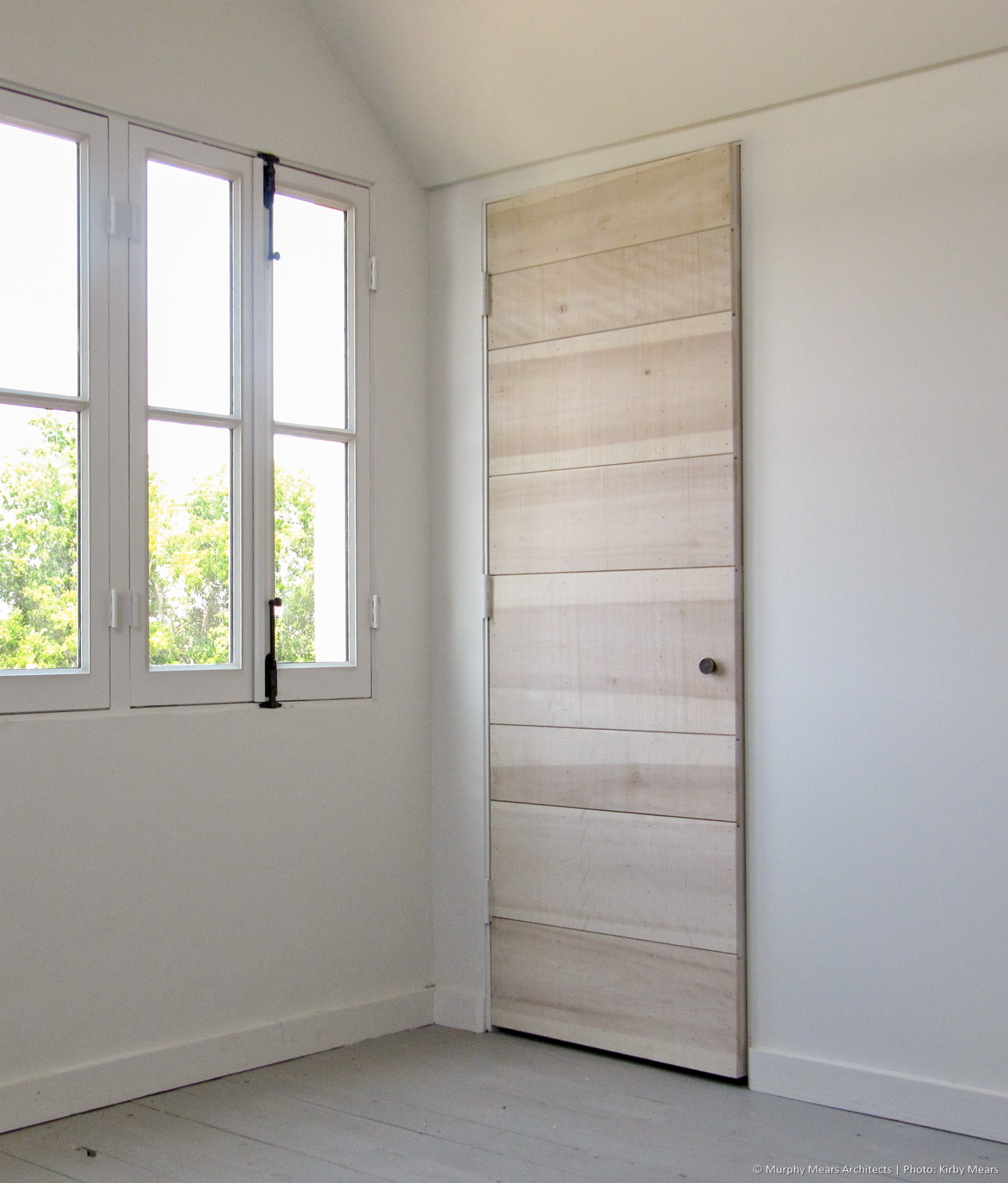 Typical interior door: custom flush wood plank construction.