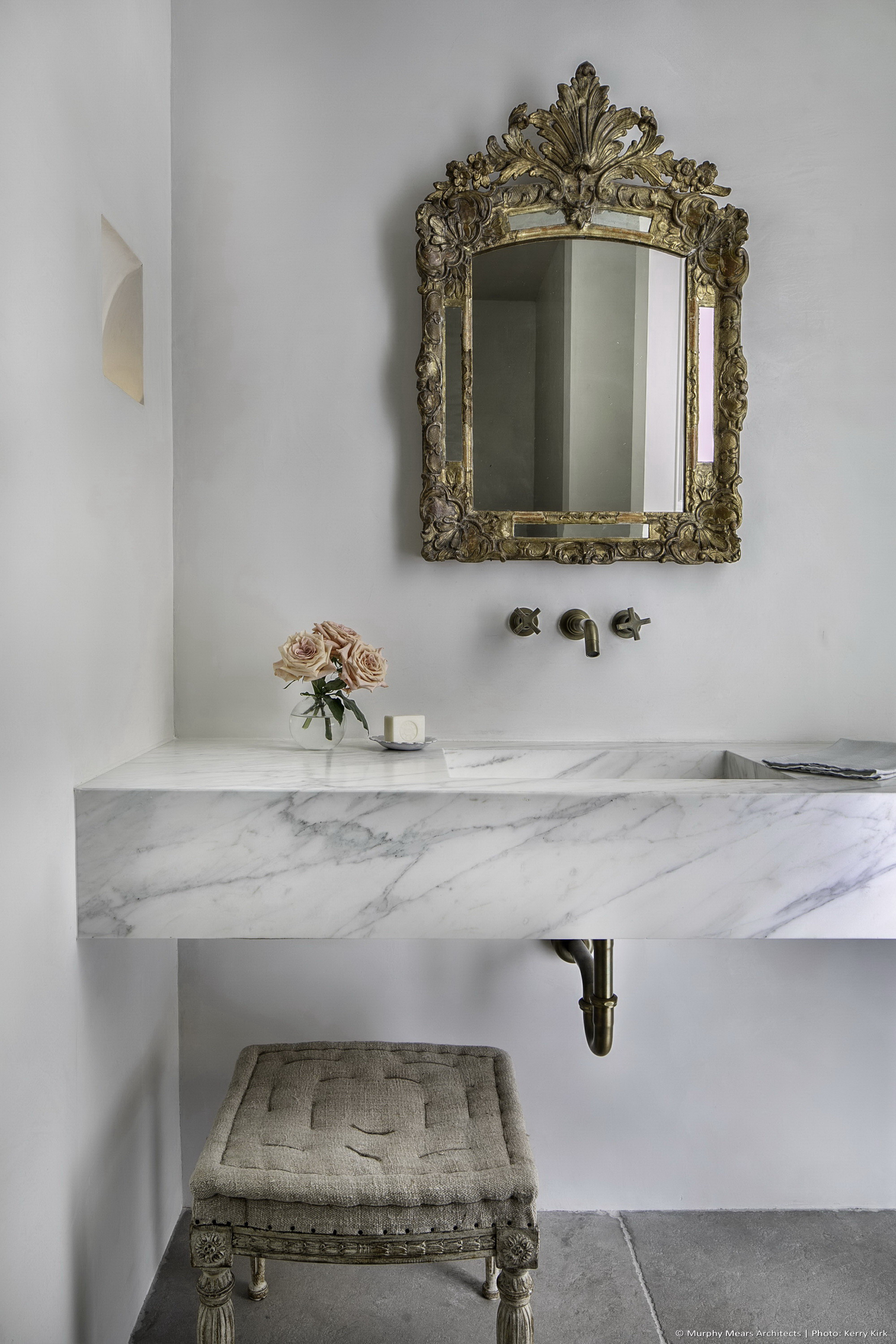 Powder room with marble sink and plaster finishes.
