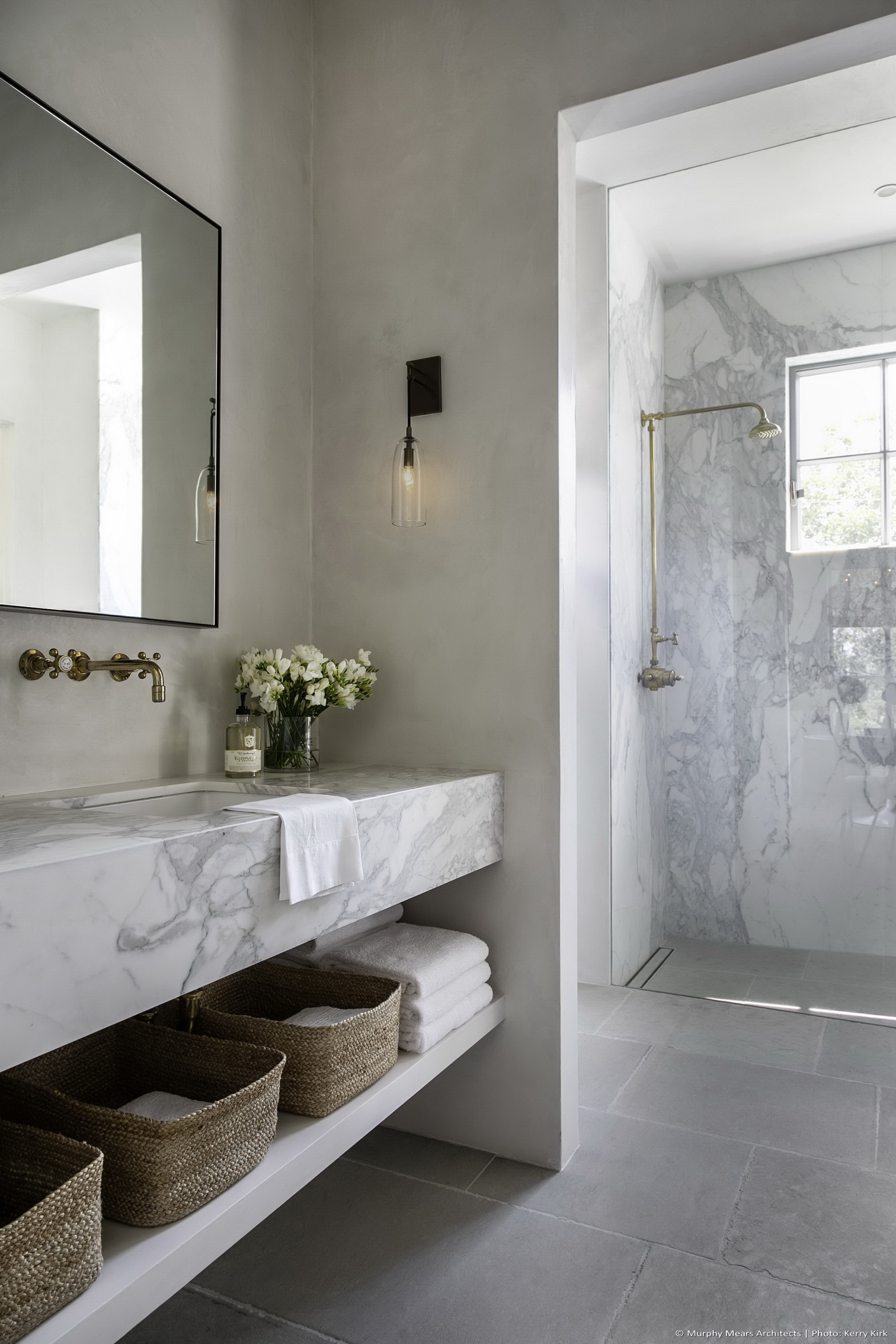 Guest bath with marble sink, plaster walls, limestone floors, and a marble shower beyond.