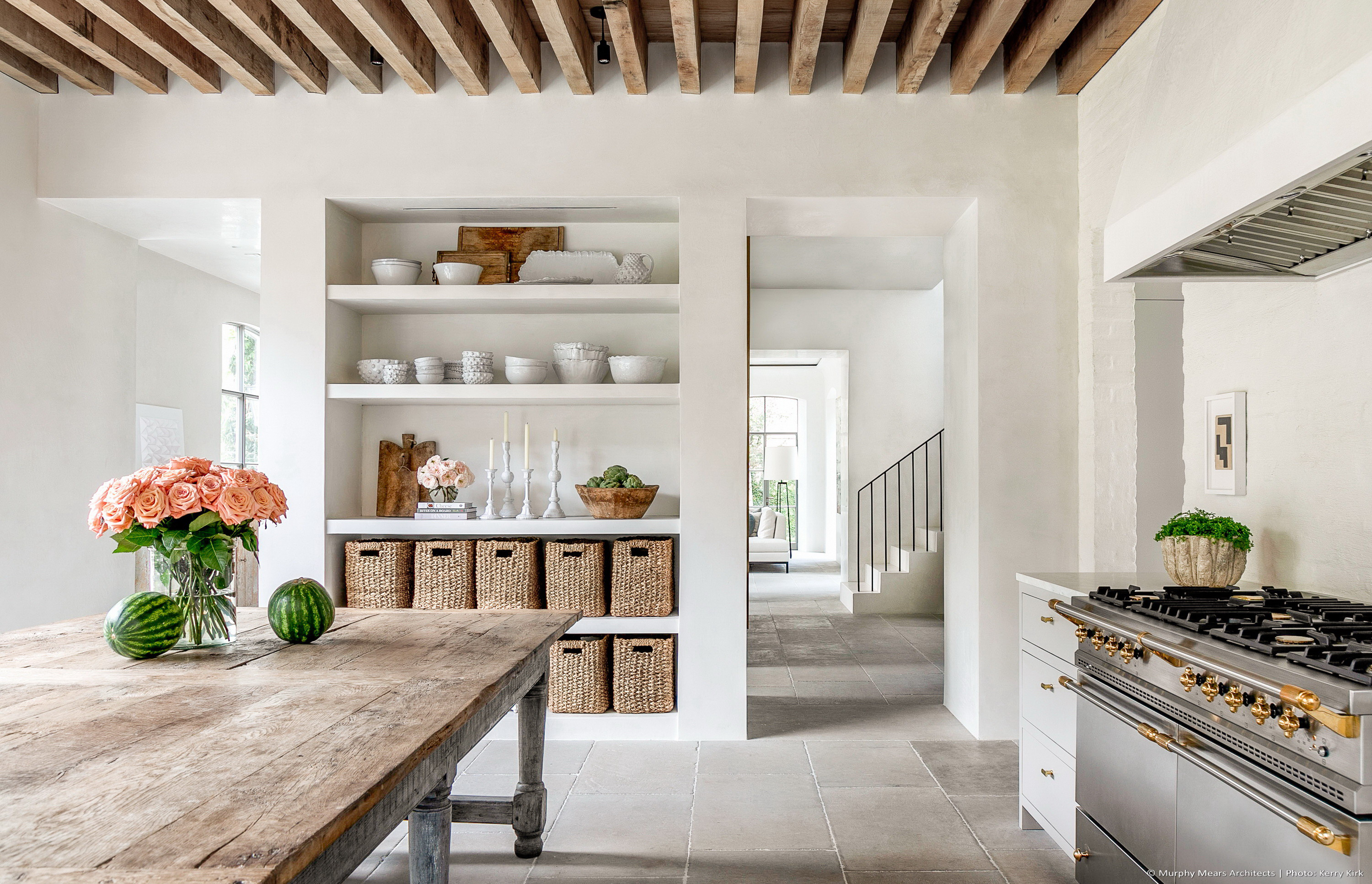 Kitchen with a central farm table, lacanche range, and load-bearing wood ceiling structure above.