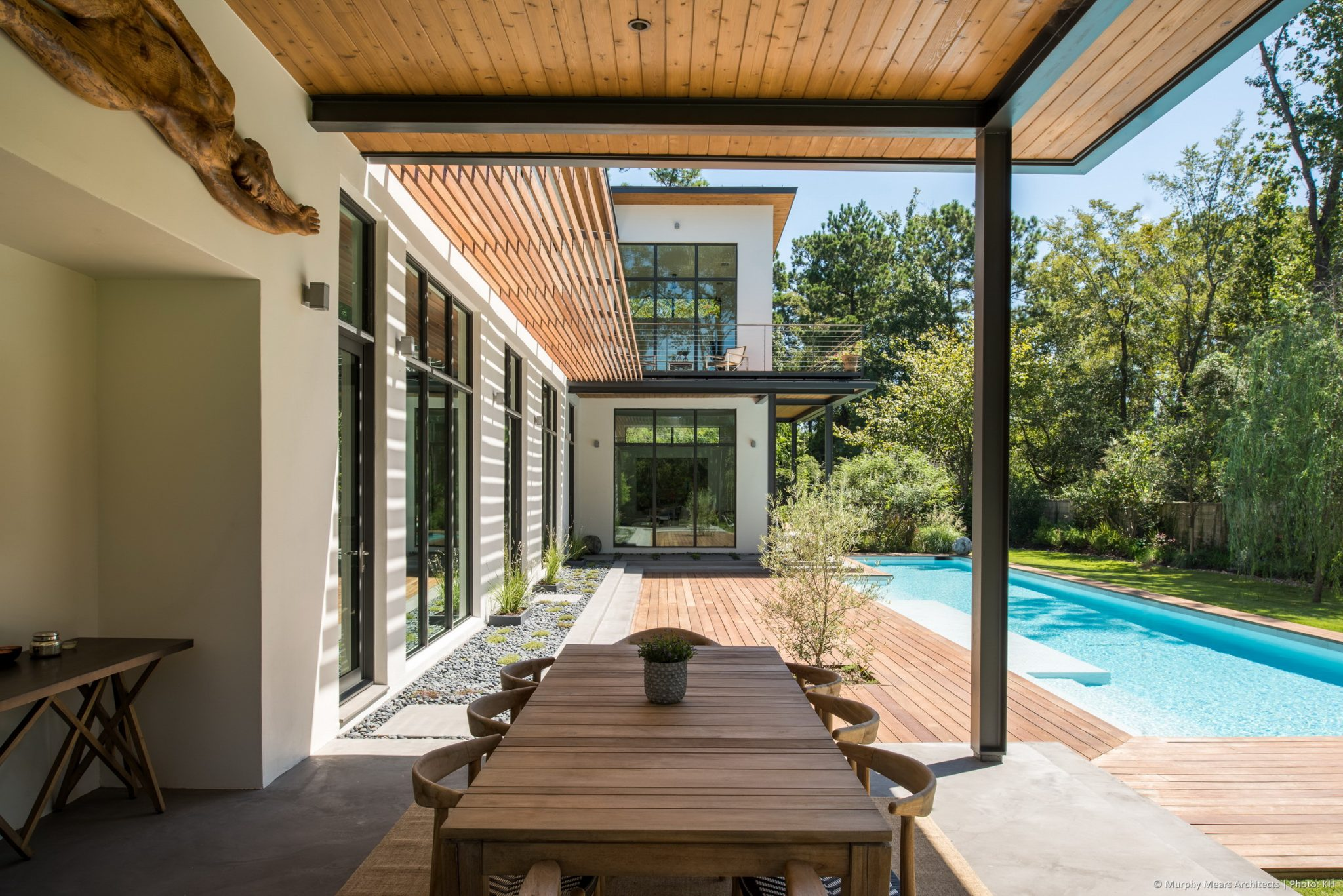 Shaded outdoor space in the covered terrace, with a view of the family room and master bedroom beyond projecting into the backyard space.