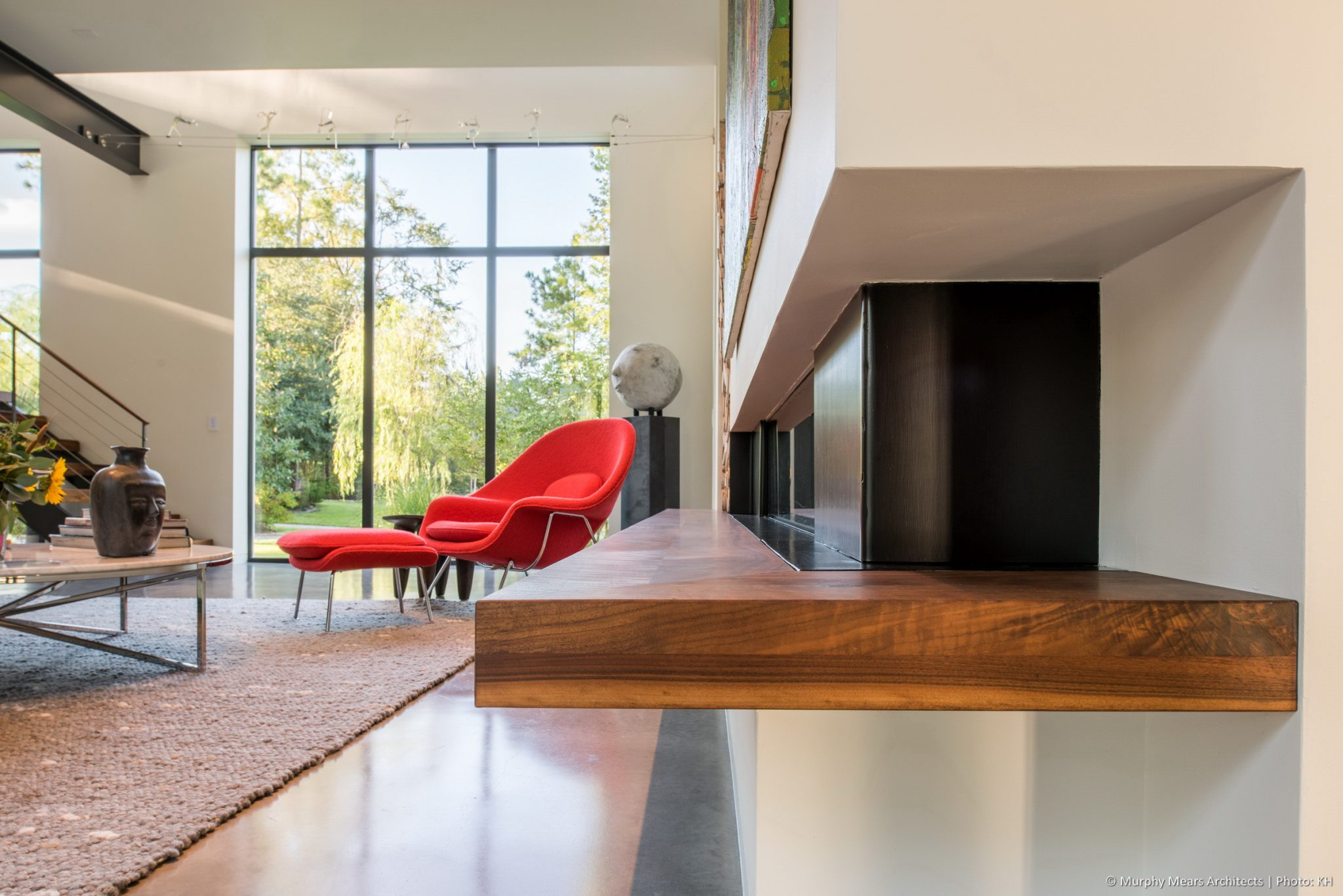 Open House - Wood and steel fireplace finishes complement the wood and steel stair beyond. A floor to ceiling window on the front aligns with an identical window on the opposite side of the room.