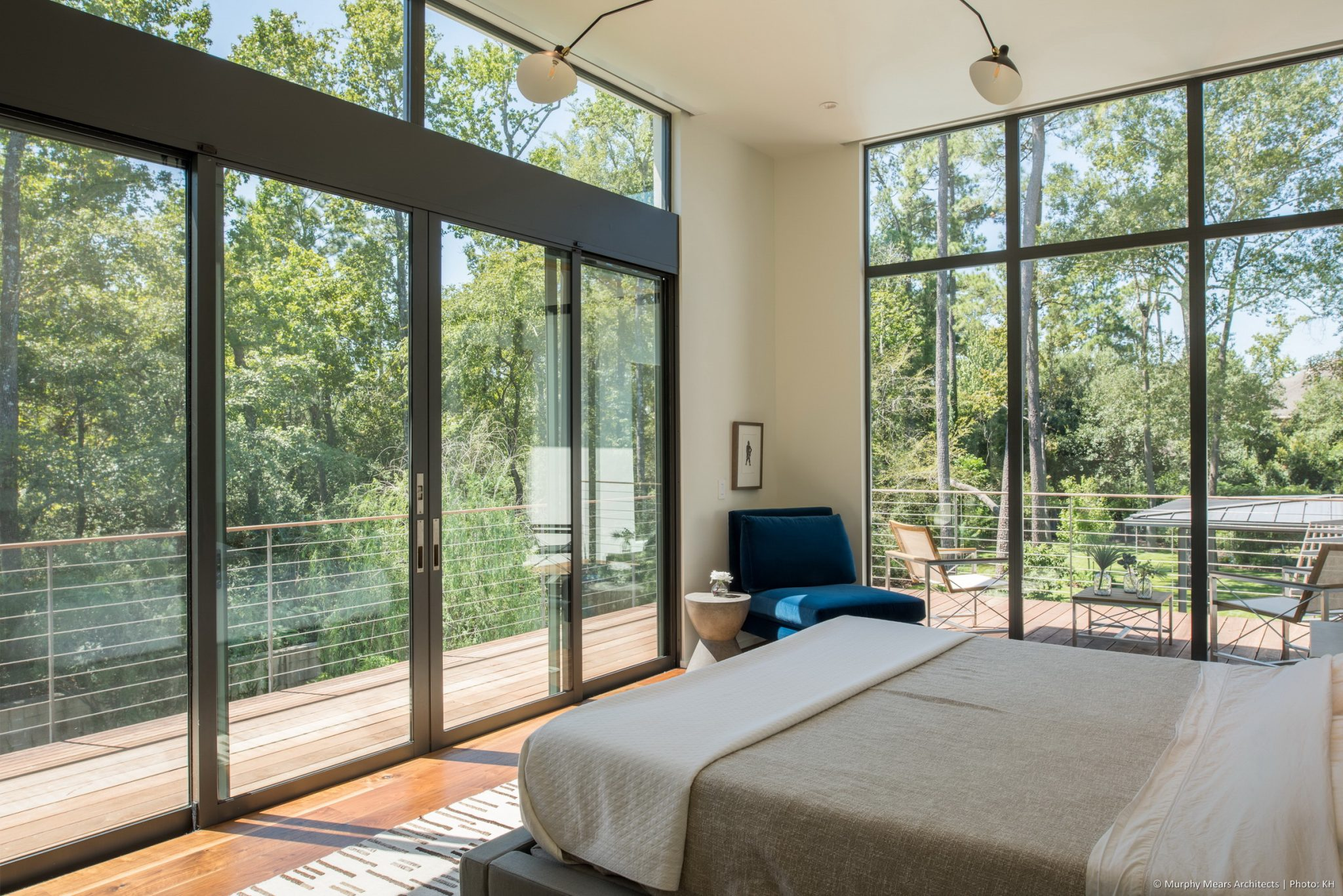 Carlton Woods Residence - Sliding glass doors open up to the wood and steel master balcony which overlooks the dense green backyard landscape.