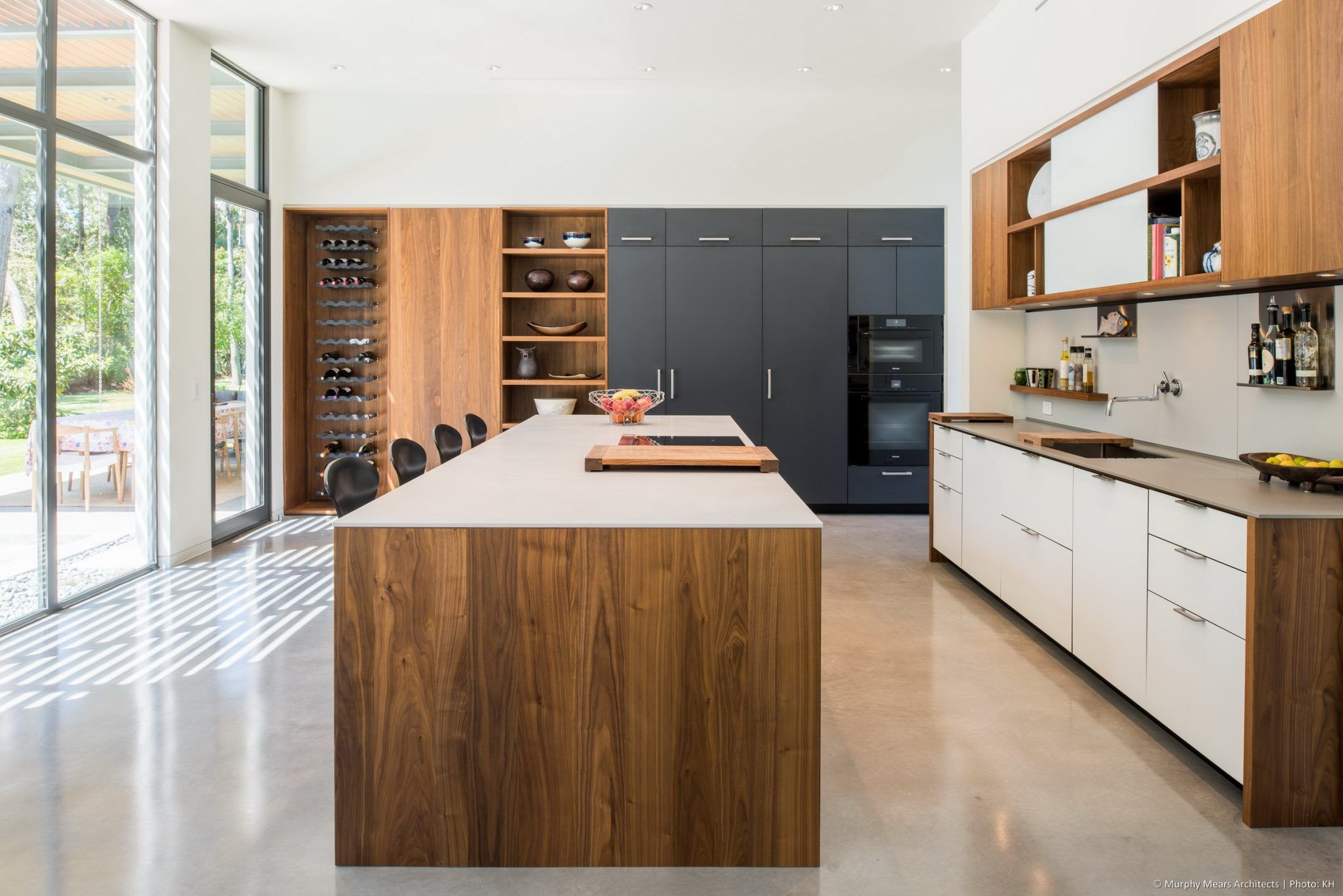 Carlton Woods Residence - A central island and two storage walls arranged for open flow through the kitchen and generous views of the backyard space.