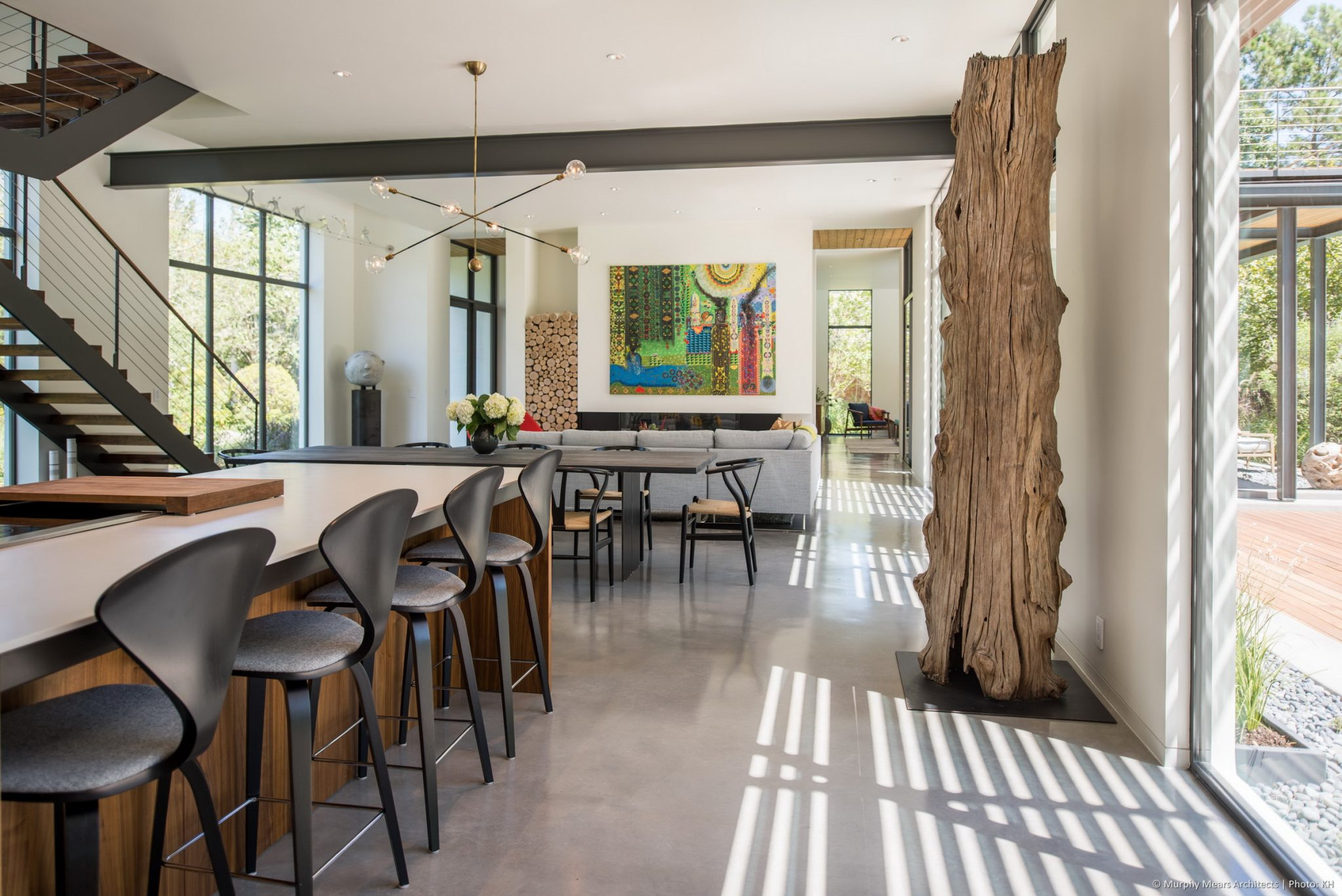 Carlton Woods Residence -  Living-dining-kitchen space with a long view across the entry and into the family room beyond.