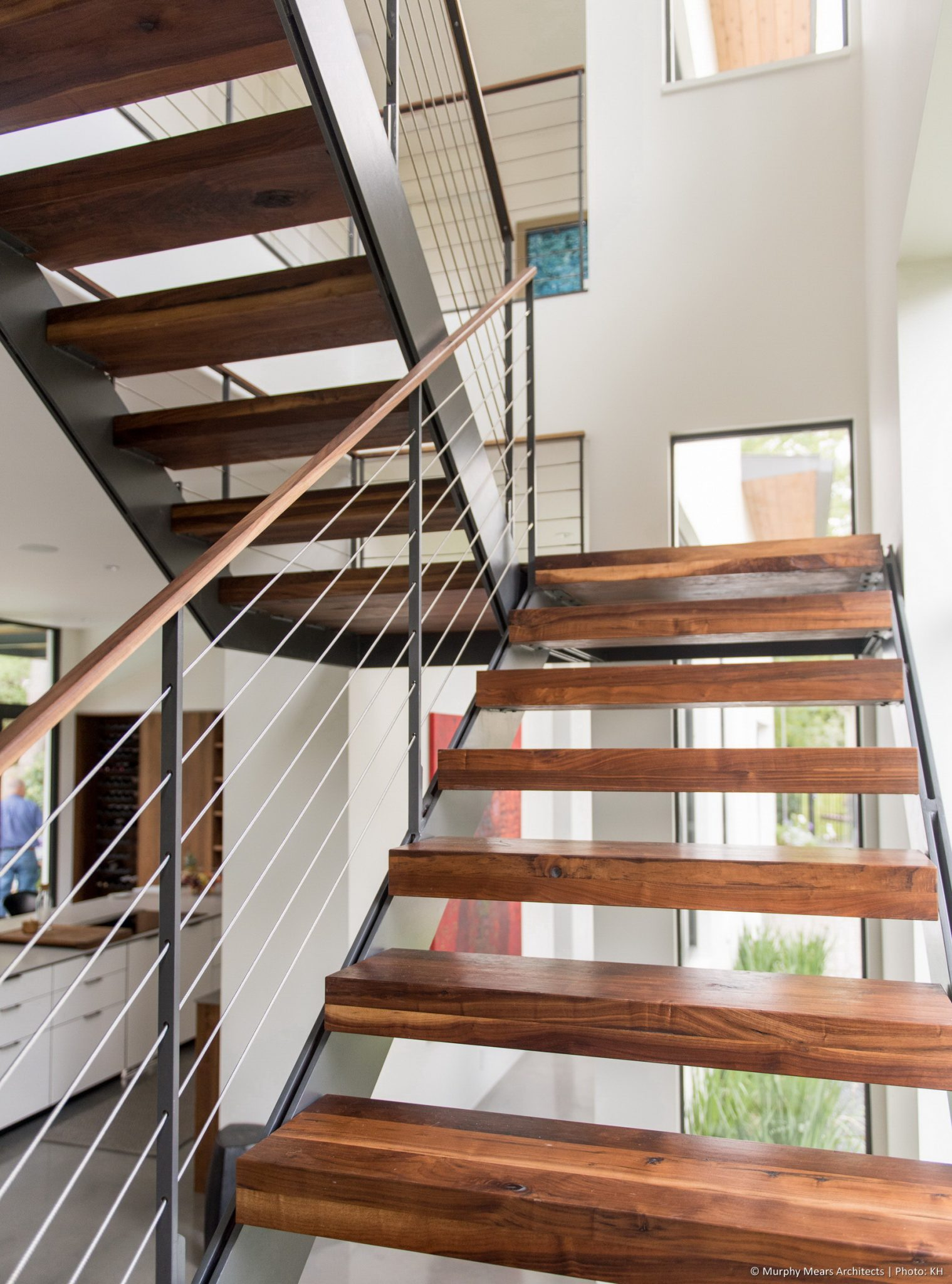 Open House - Open stair with walnut treads and steel stringers floating in the corner of the living-dining space.