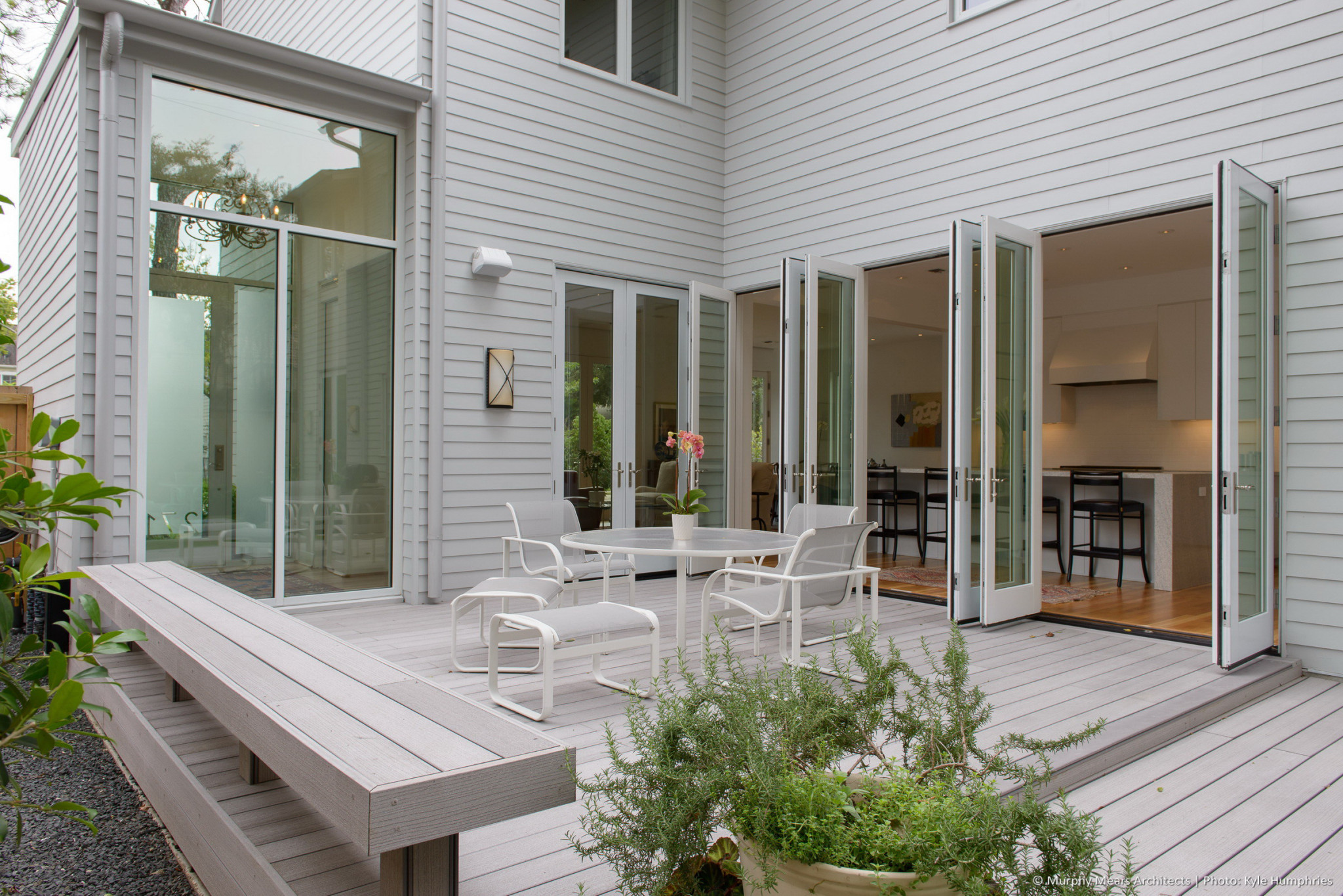 composite wood deck bordered by bench, storefront entry windows and french doors opening into kitchen