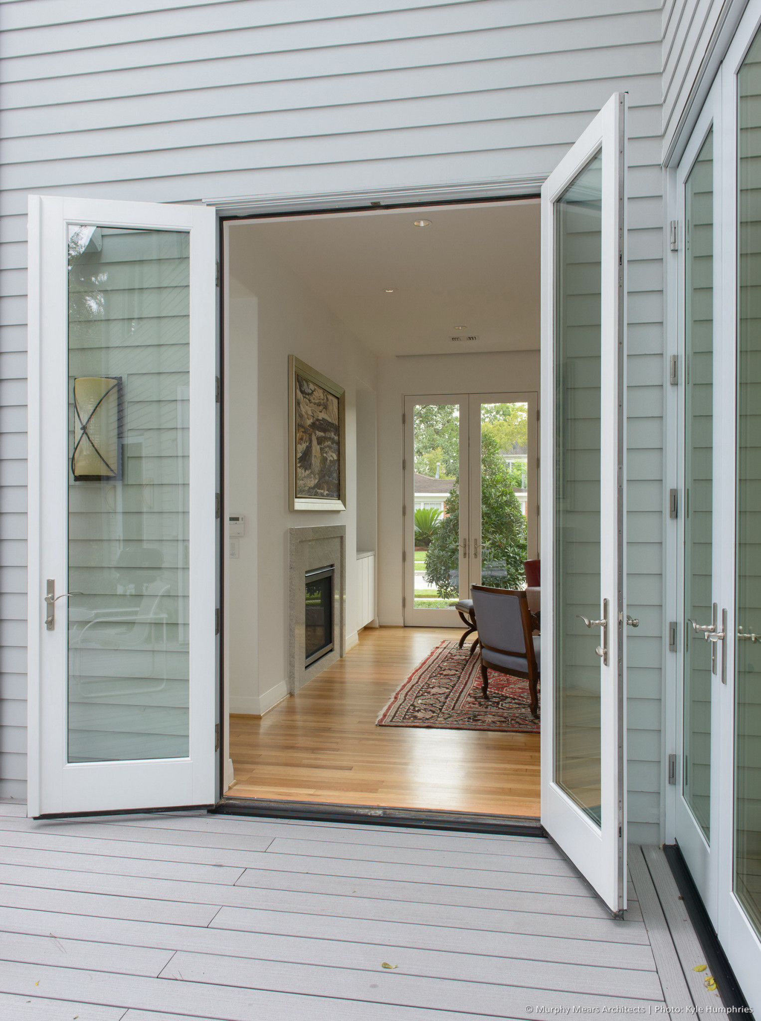 french doors on deck open to living room with doors aligned at front of house beyond