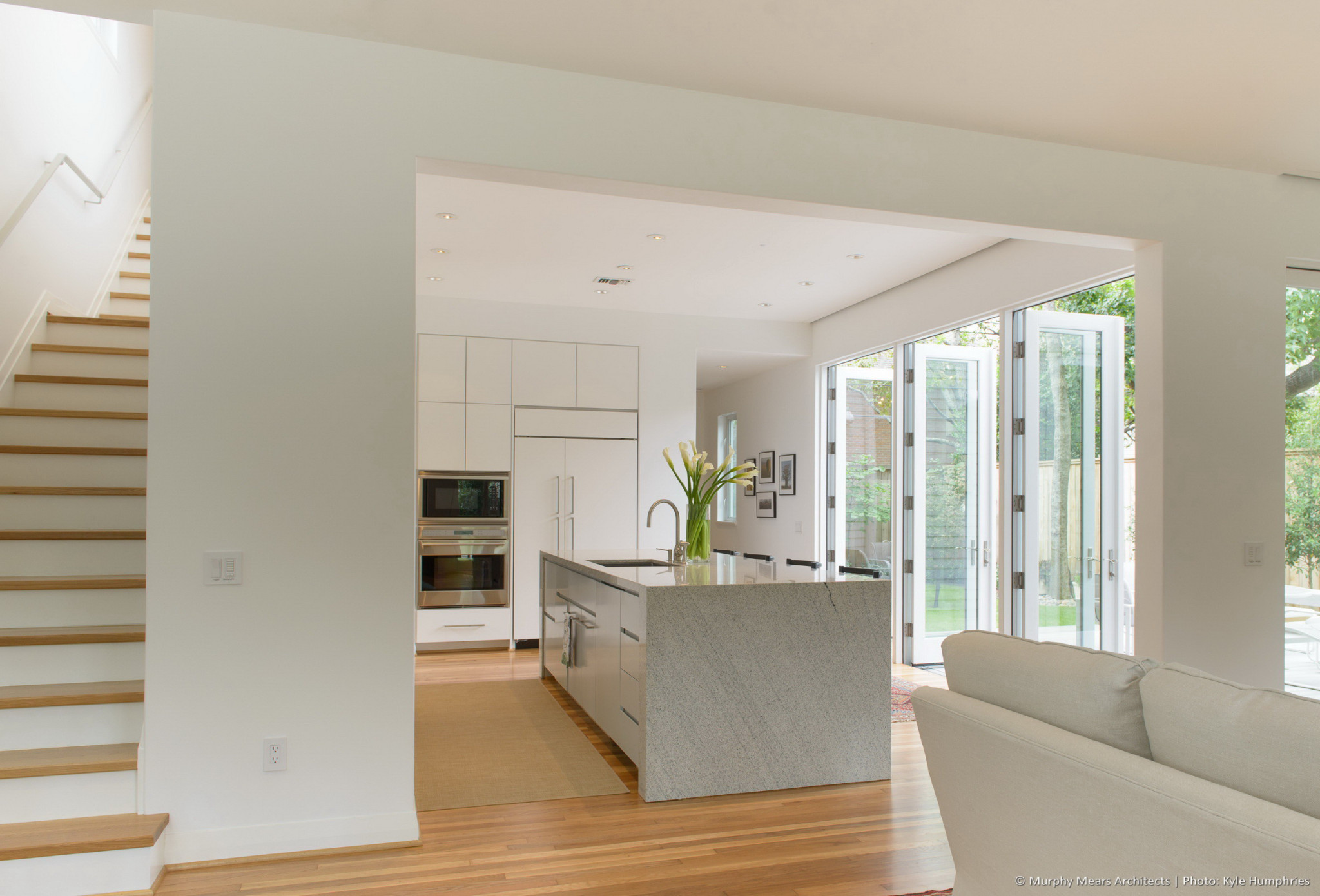 kitchen viewed from dining area with doors open to back yard and stair rising behind