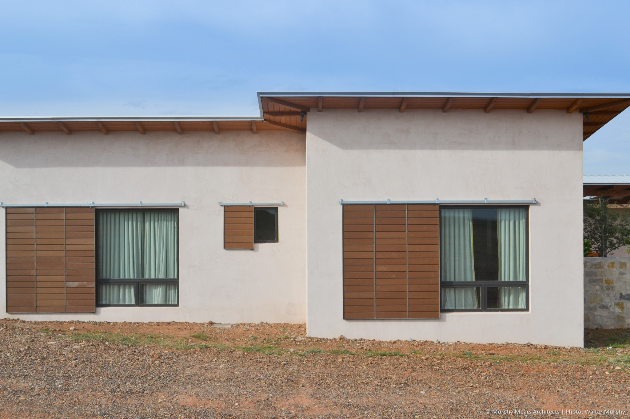 la habra stucco finish walls with galvanized steel and composite wood plank rolling window shutters