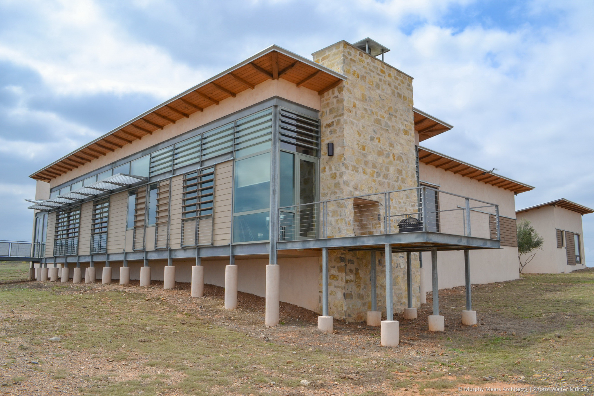 galvanized steel deck on piers wrapped around stone fireplace on end of main house