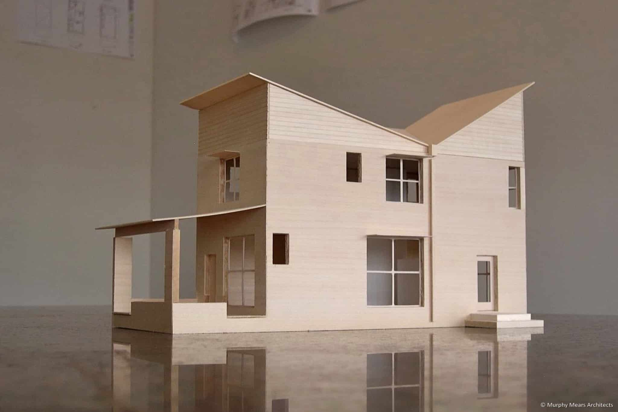 Wood model of AAC block house with rainwater-collecting butterfly roof.