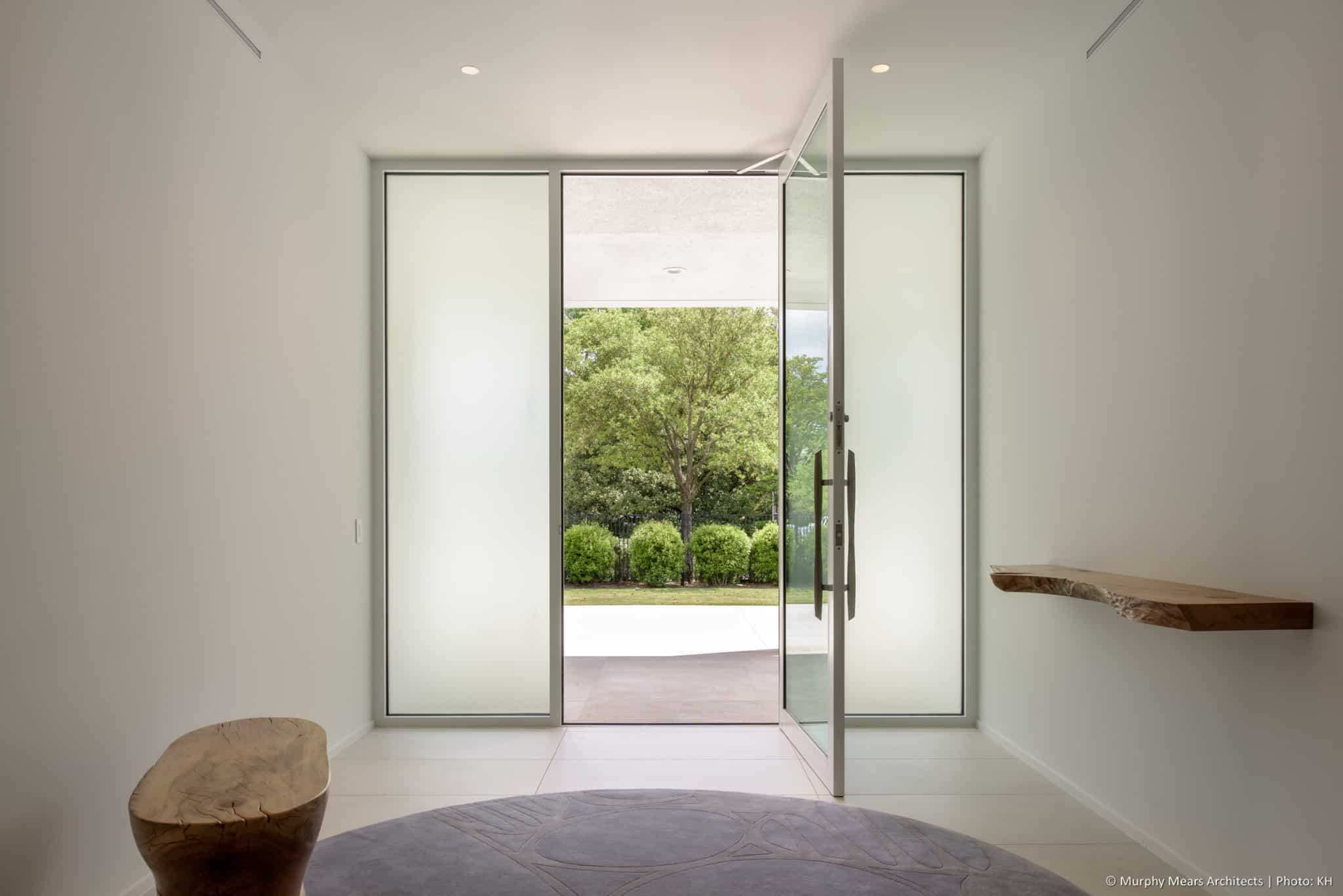 Frosted glass front entry door and sidelites, on the central axis through the home.