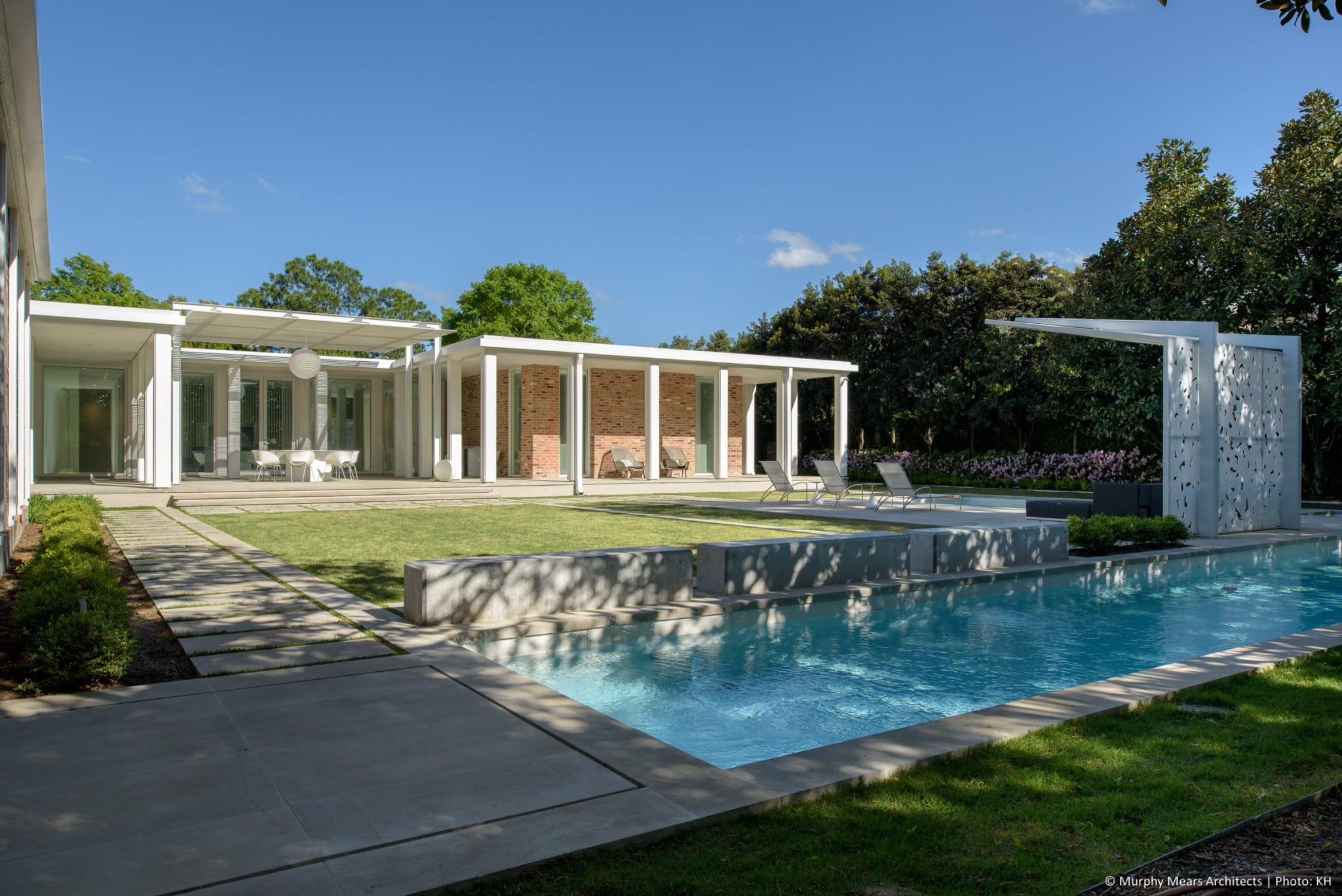 Limestone paths, concrete benches, a lap pool and a pool deck surround the axial central lawn.