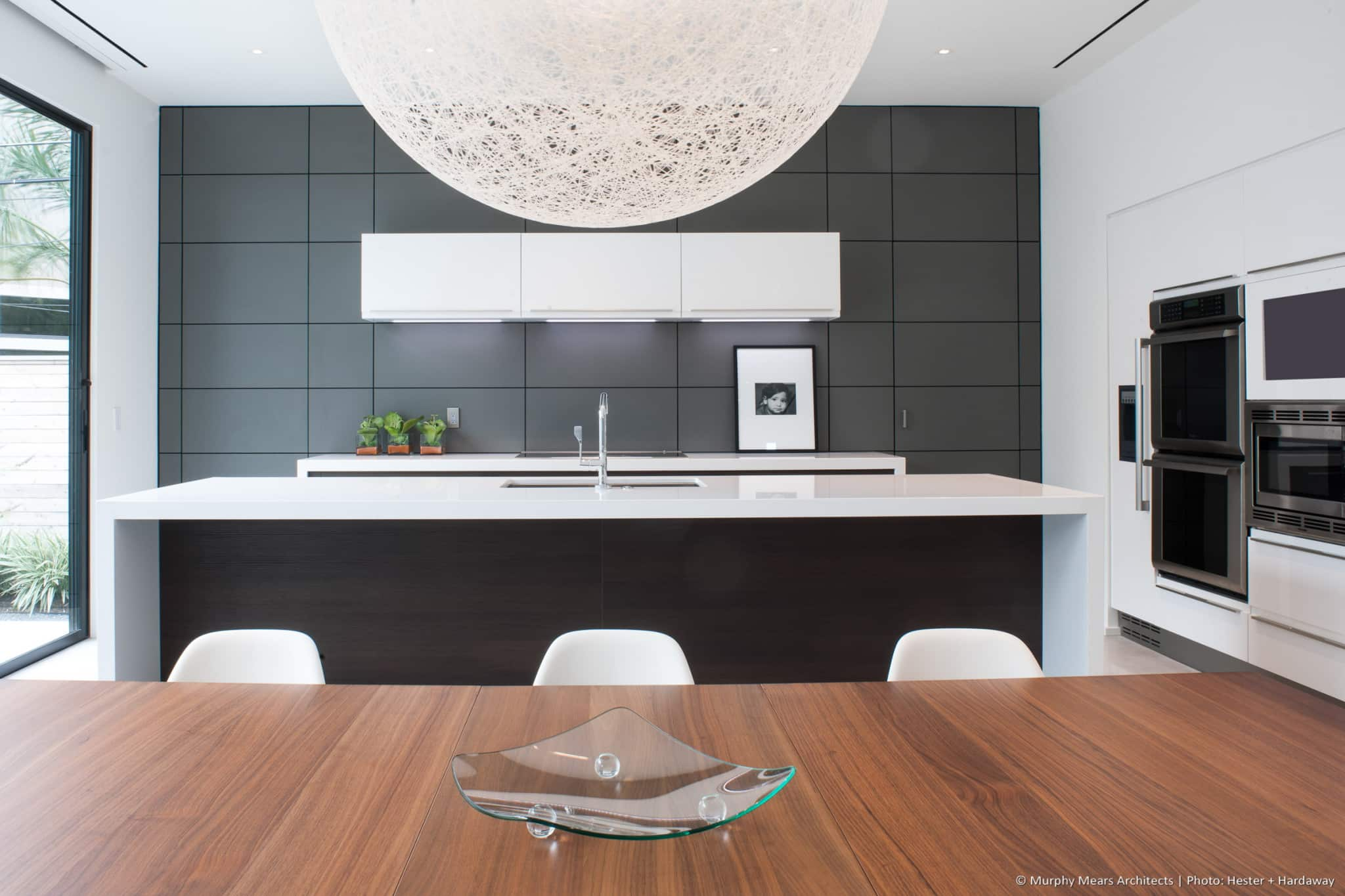 Dining table, kitchen island and back counter along the central axis of the open living-dining-kitchen, with a wall-grid responsive to integrated components.