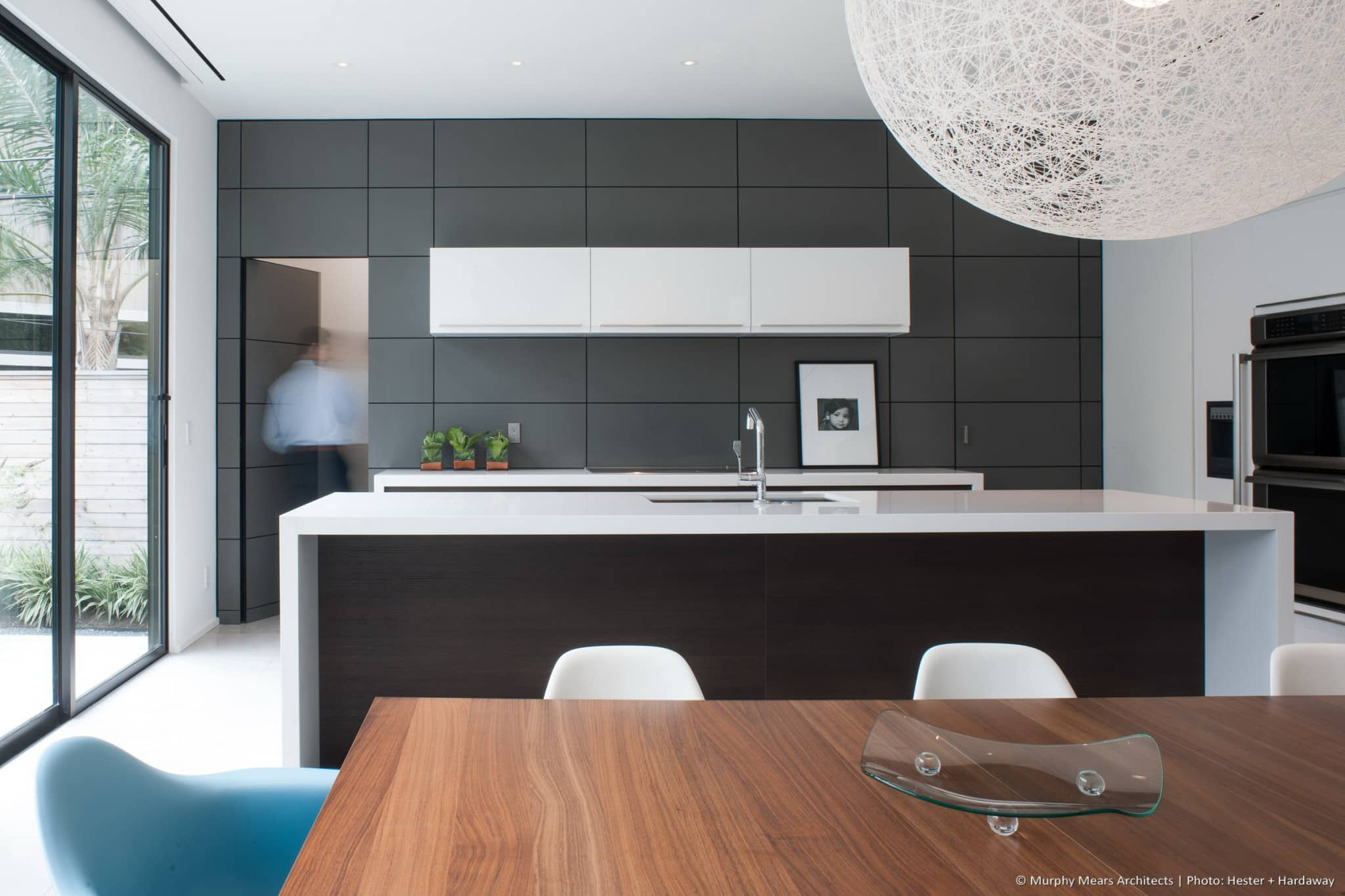 Hidden door within the kitchen wall panels provides access to pantry storage beyond.