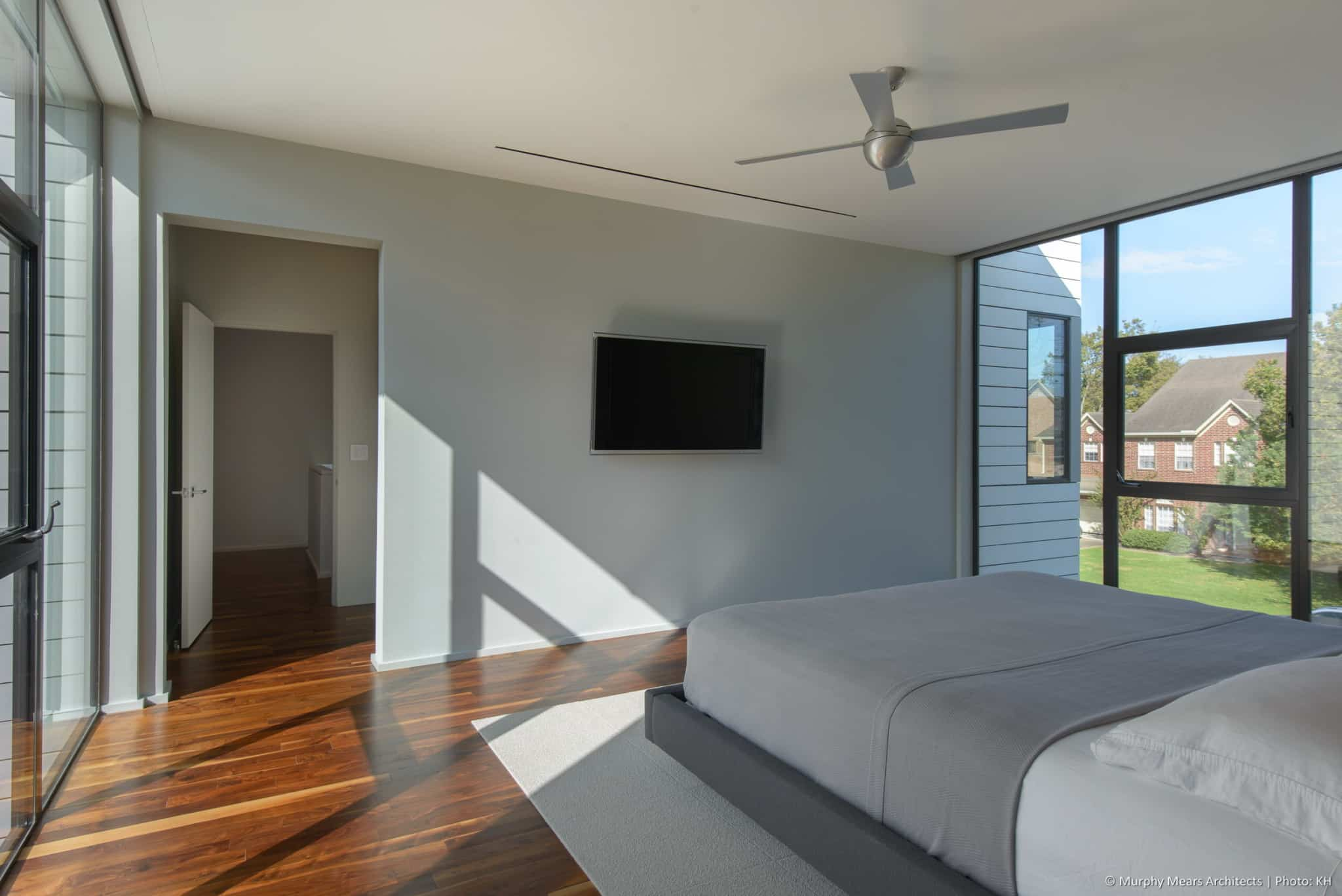 Sheer and blackout roller shades raised into concealed pockets for North and South views from the master bedroom.