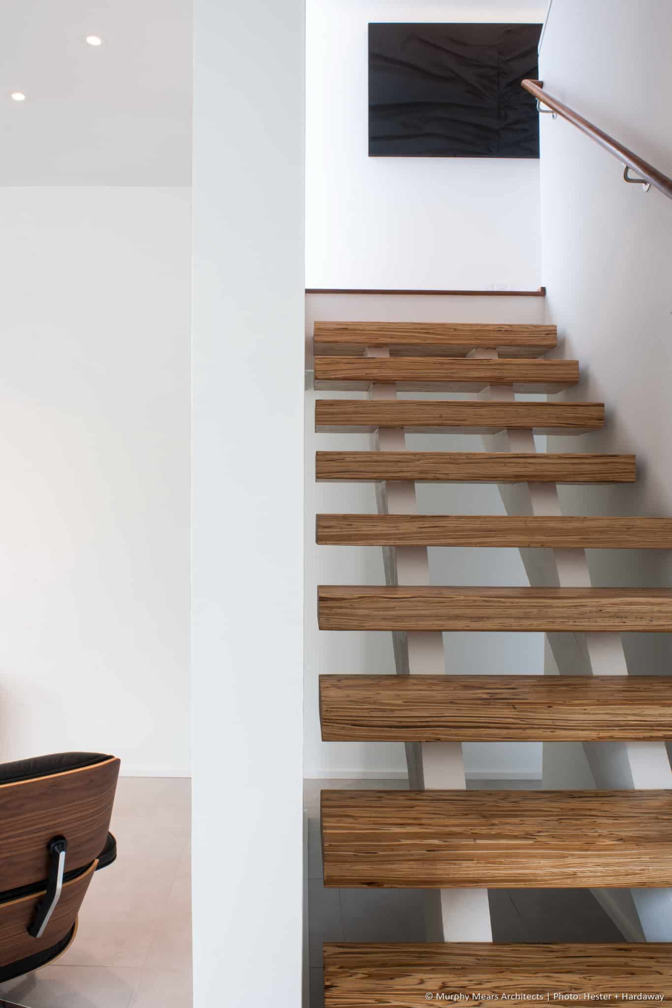 Open wood stair treads, with the passage to the A/V area visible below the intermediate stair landing.