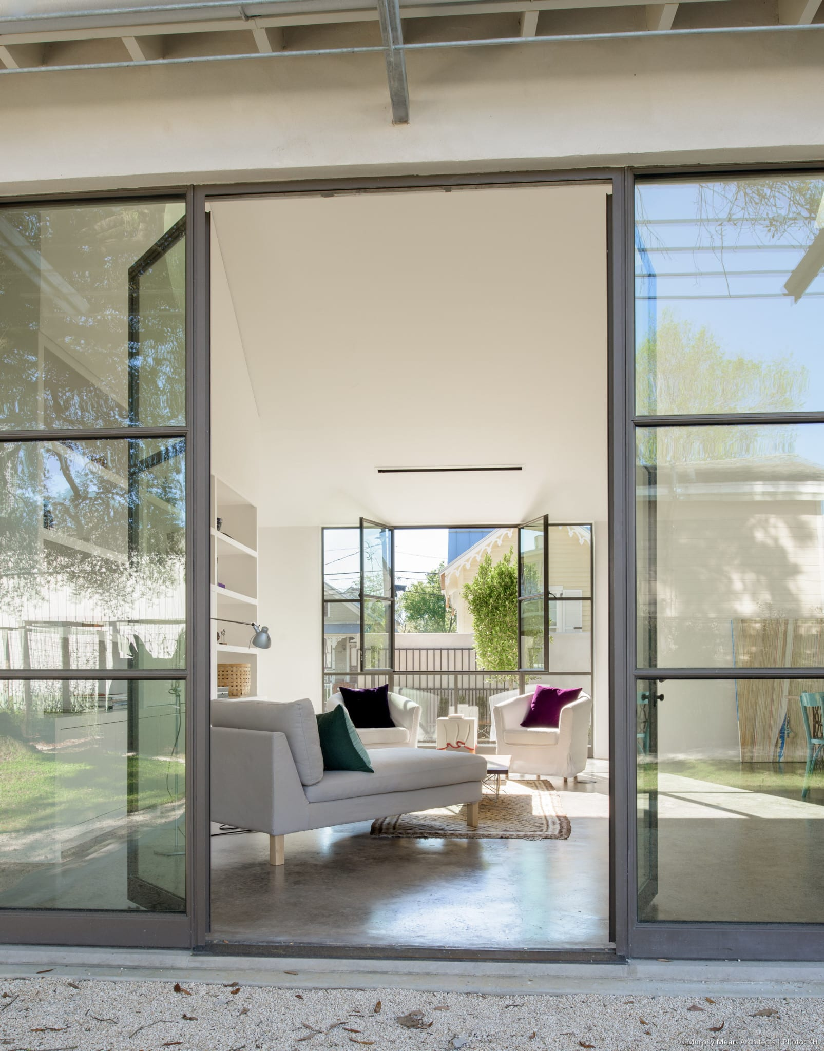 Doors and windows open to the front and back courtyards on each side of the living-dining-kitchen space.