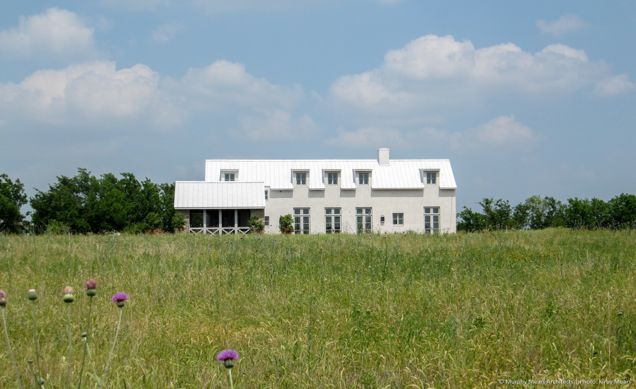 Farmhouse at the top of a gentle hill, with 360-degree views of the property.