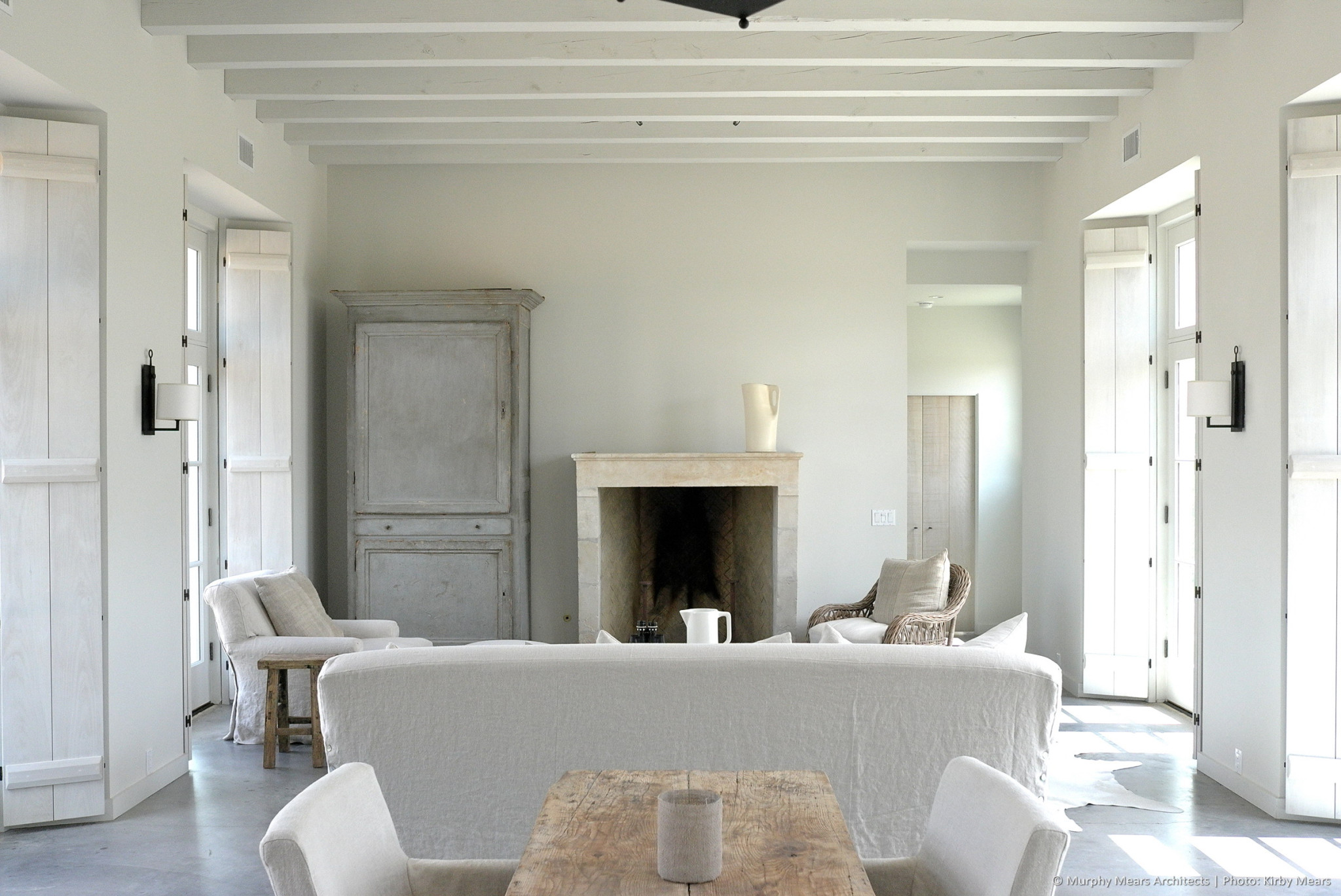 Living Room with white-washed ceiling beams and window shutters.