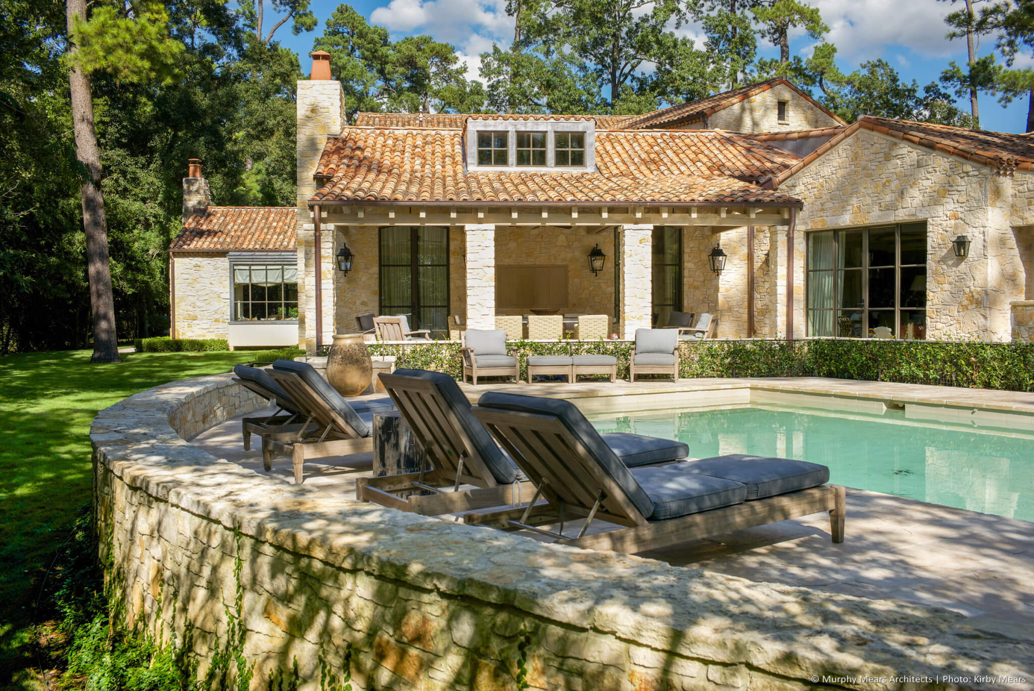 Stone pool terrace, with covered porch, family room and kitchen beneath the one-story clay-tile roofs beyond.
