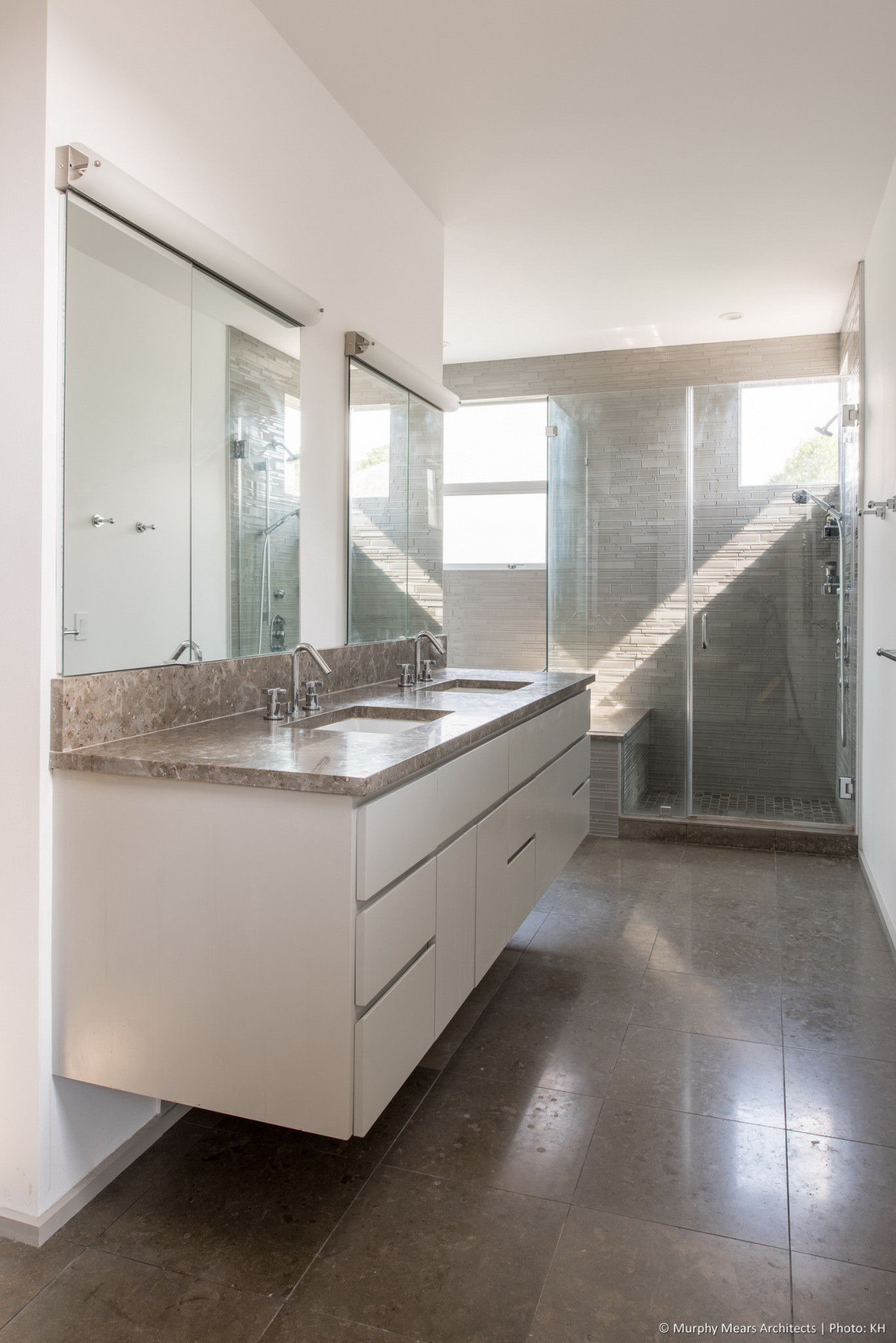 Master bath, lit by afternoon sun through corner windows over the shower and tub area.