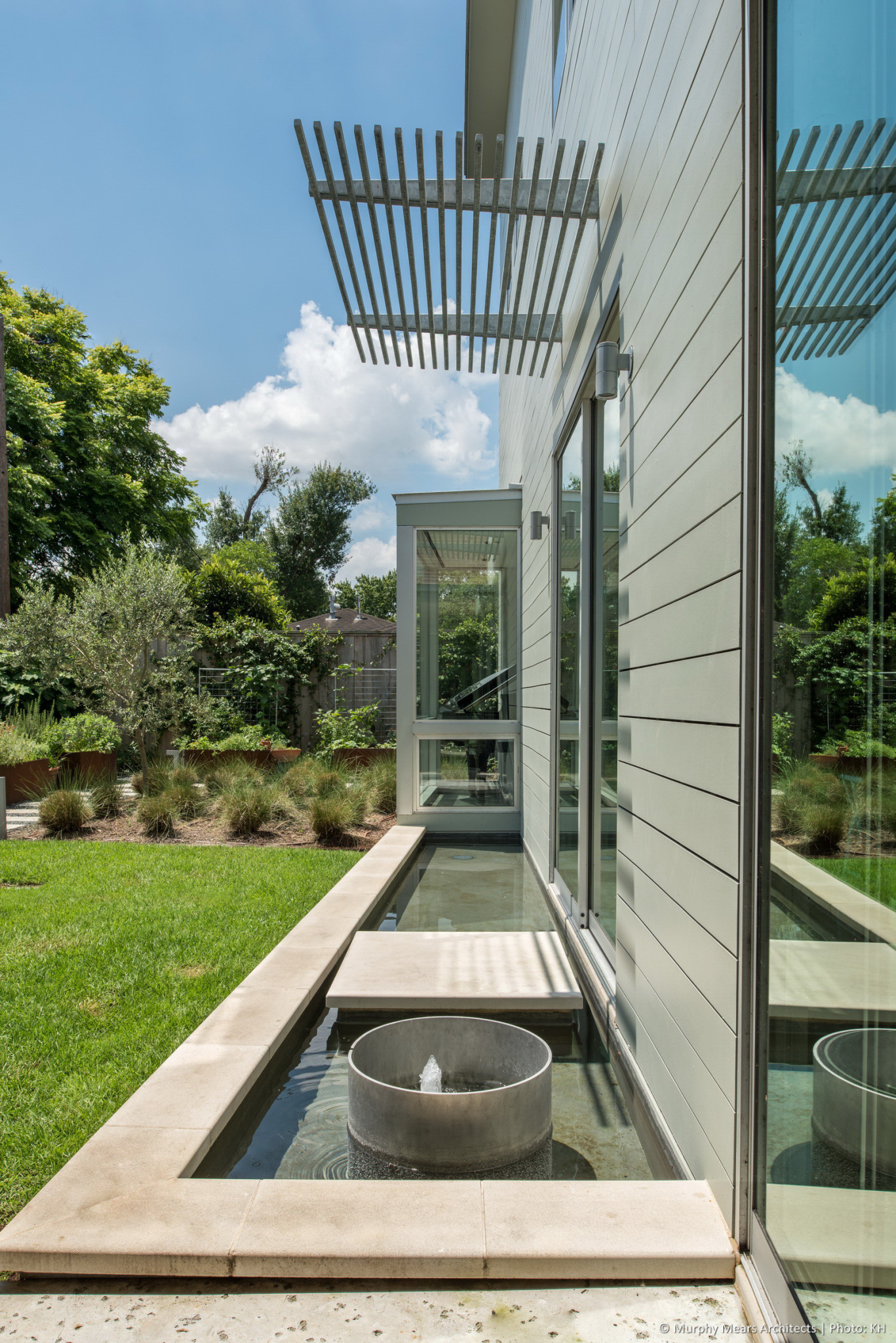 Water feature continues the central site axis through the East garden, towards the Living Room bay window.