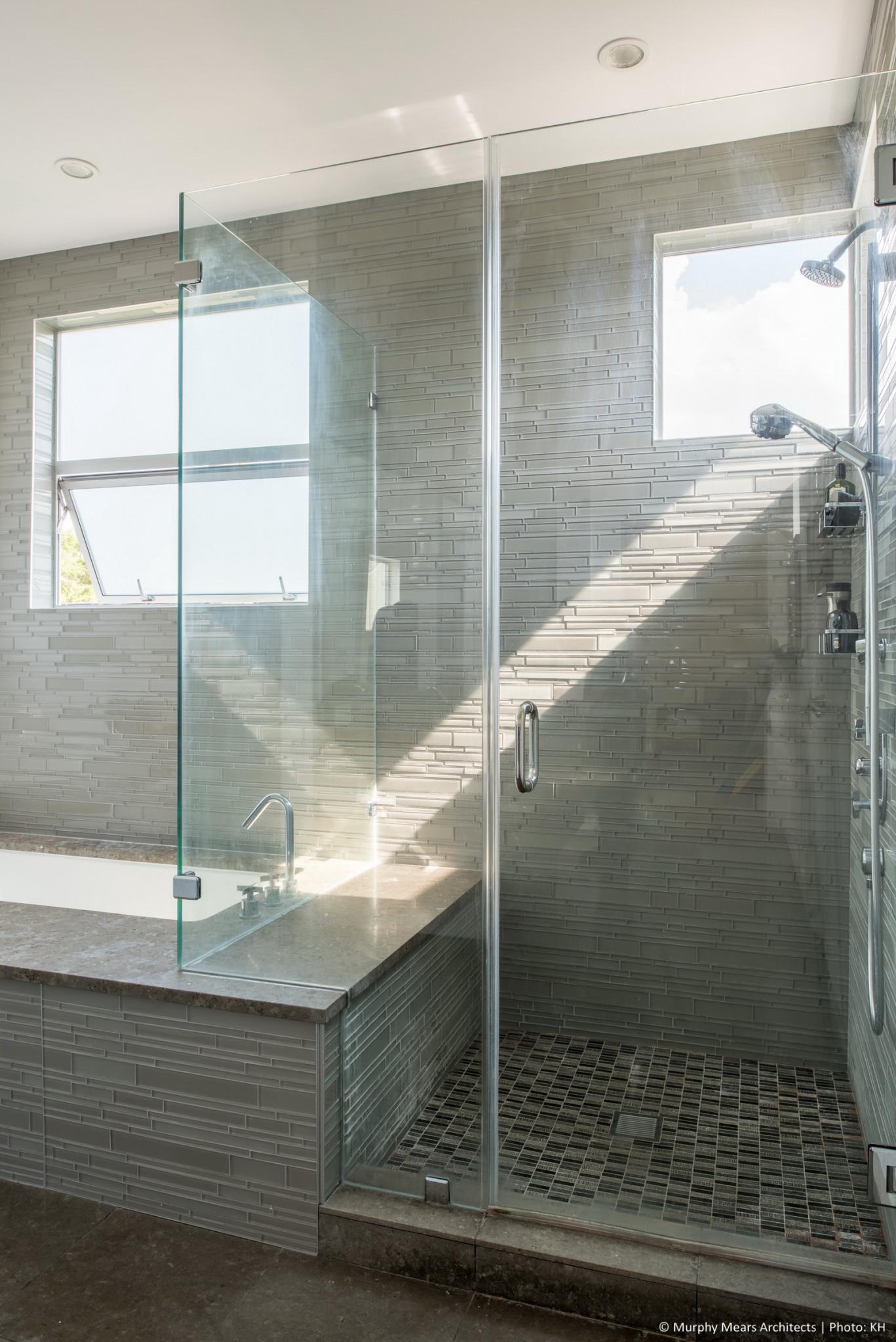 Natural light through the high corner windows over the master shower.