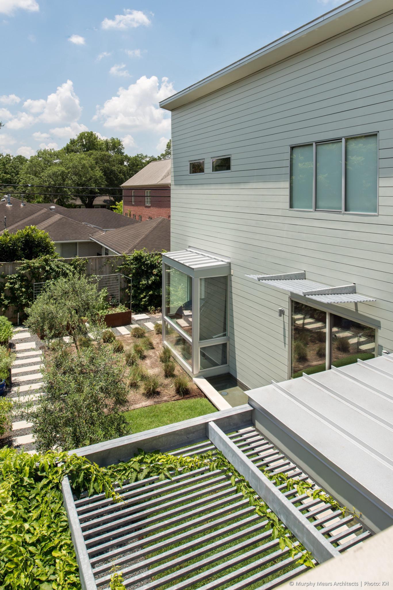 2nd floor terrace, overlooking 1st floor outdoor seating trellis and East garden beyond.