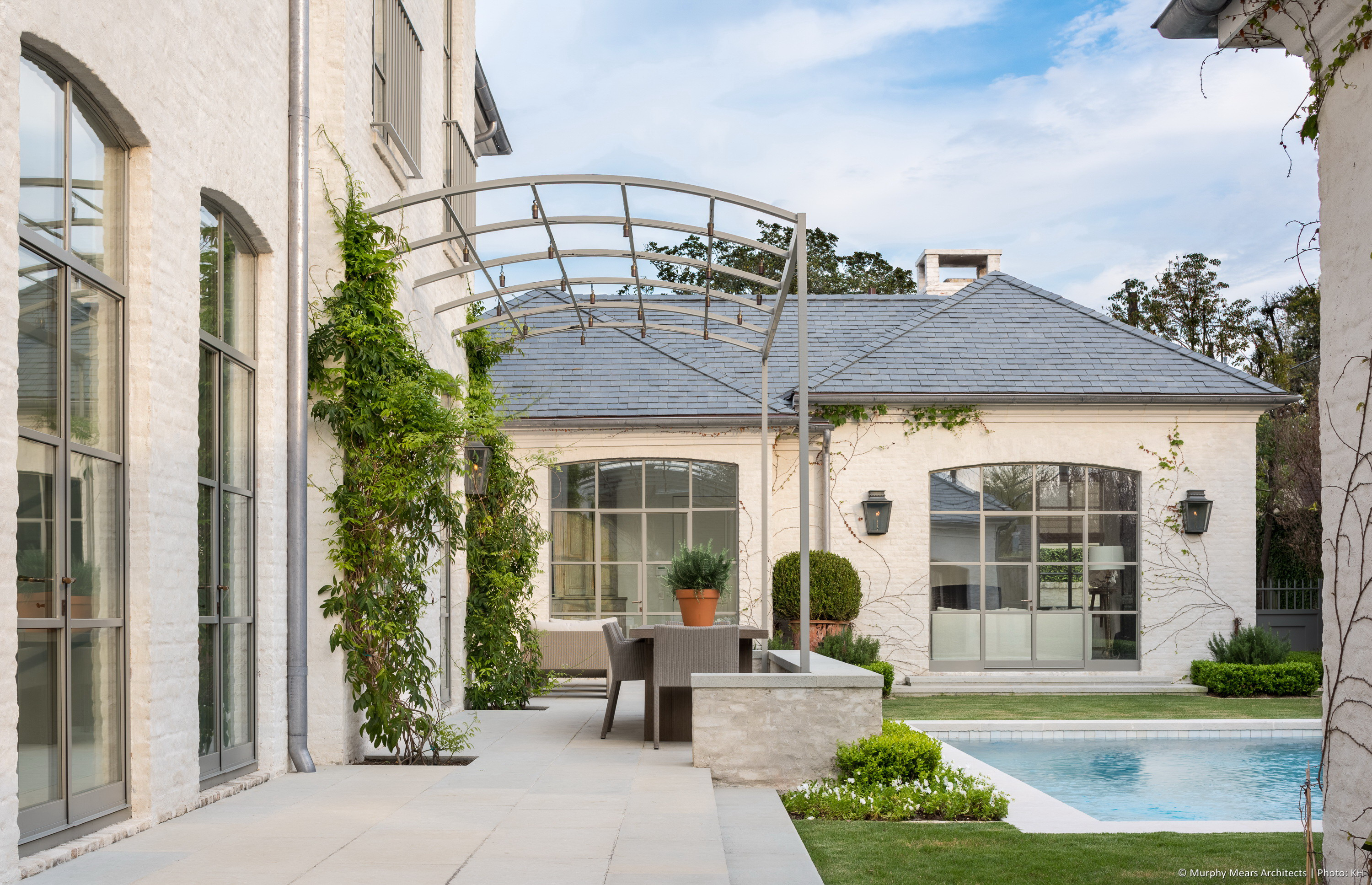 Back terrace with outdoor dining beneath a trellis that will be covered in Boston Ivy, overlooking a soaking pool set within a Zoysia lawn.