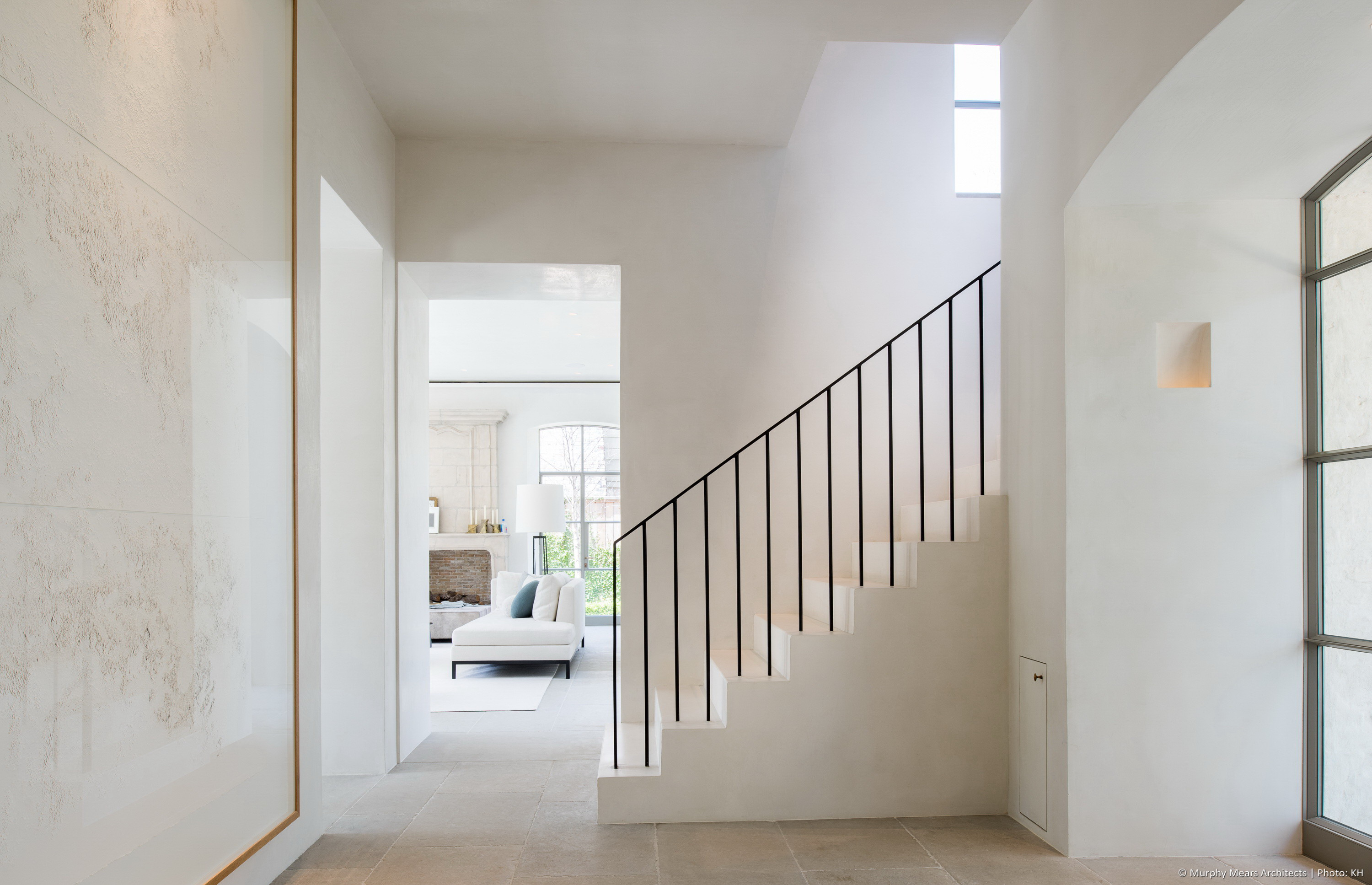 Front entry hall with a plaster stair, and an opening to the living room beyond.