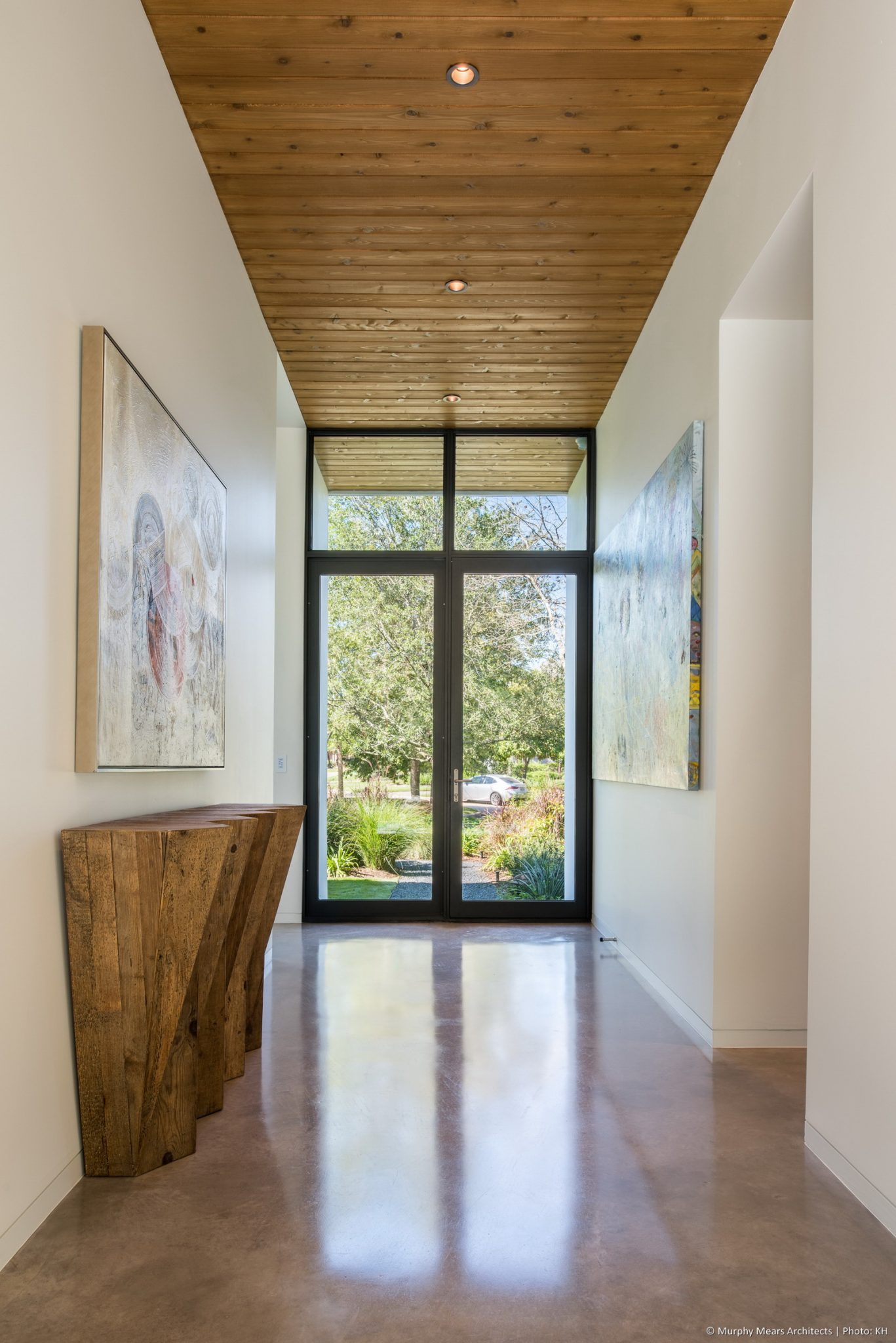 Carlton Woods Residence - Transparent front entry corridor with a ribbon wood ceiling passing through the interior and out to the back terrace.