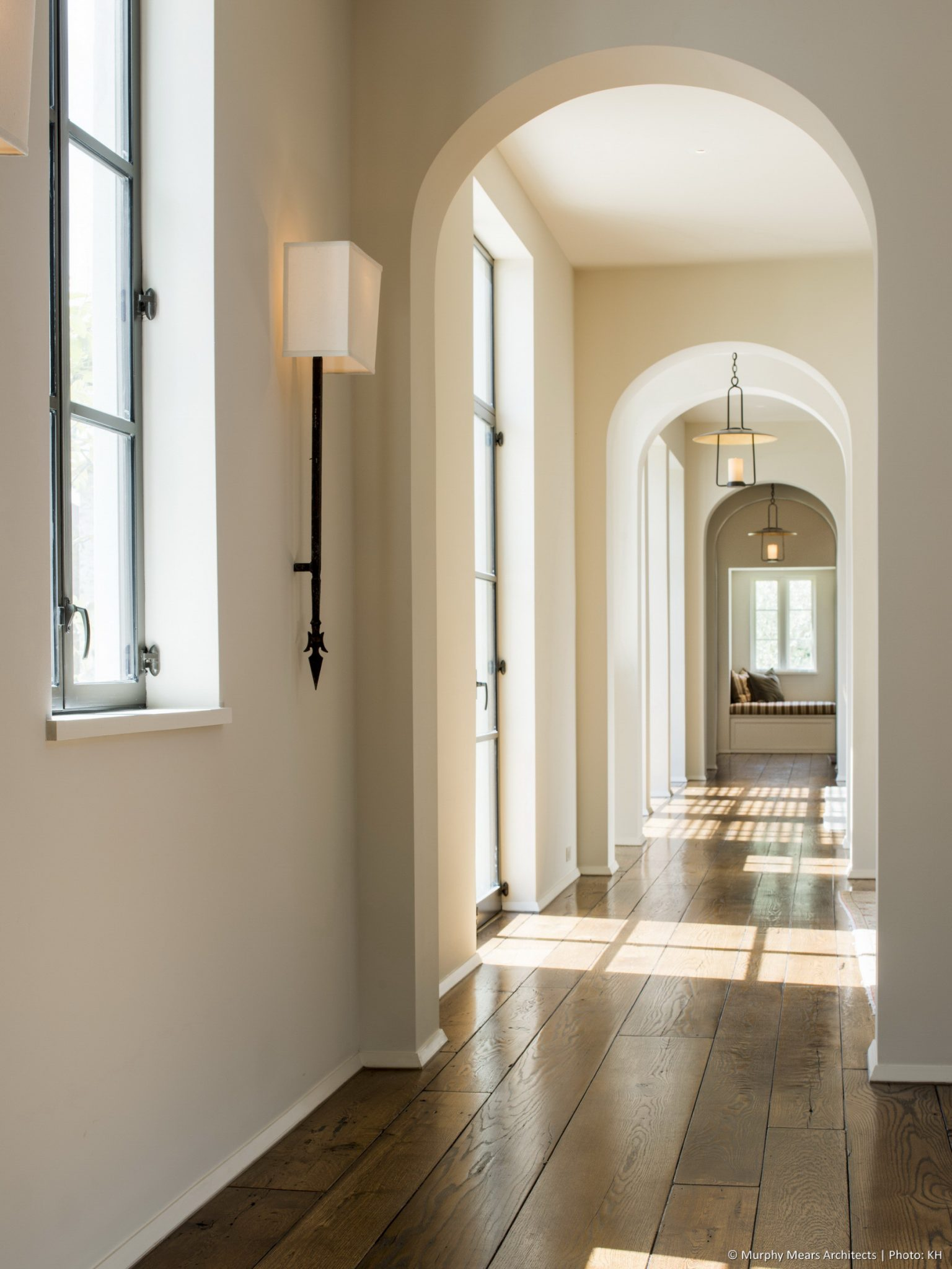 Courtyard House - Looking South along the main corridor, with morning light cast through steel windows and doors.