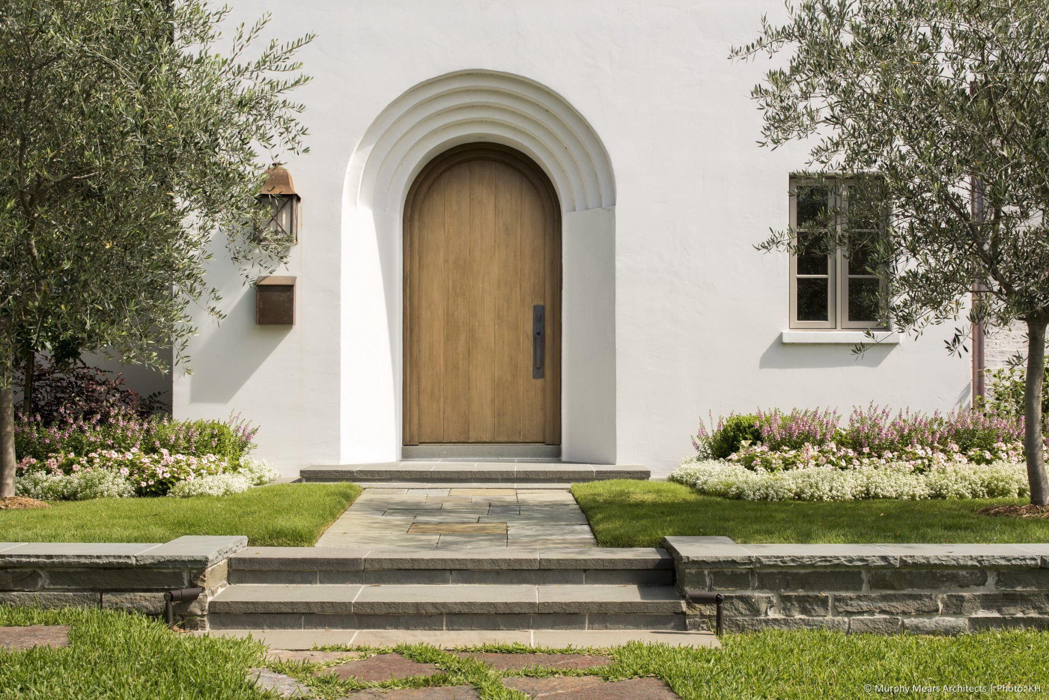 Courtyard House - Solid wood front entry door accessed from a raised front garden.